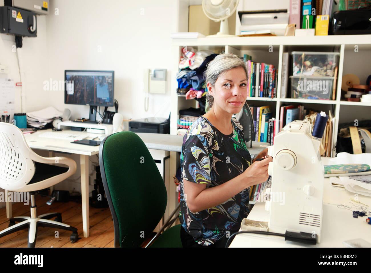 Designer travaillant dans machine à coudre dans studio Photo Stock