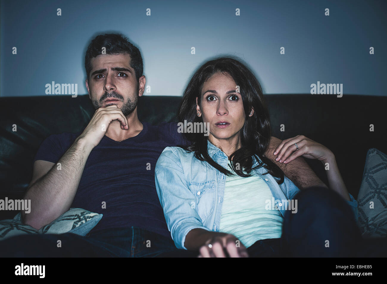Couple watching thriller sur canapé Photo Stock
