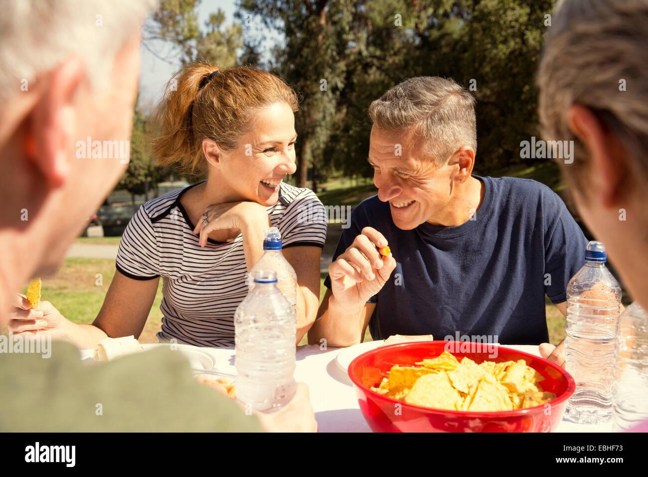 Quatre amis adultes matures chatting over déjeuner pique-nique dans le parc Photo Stock