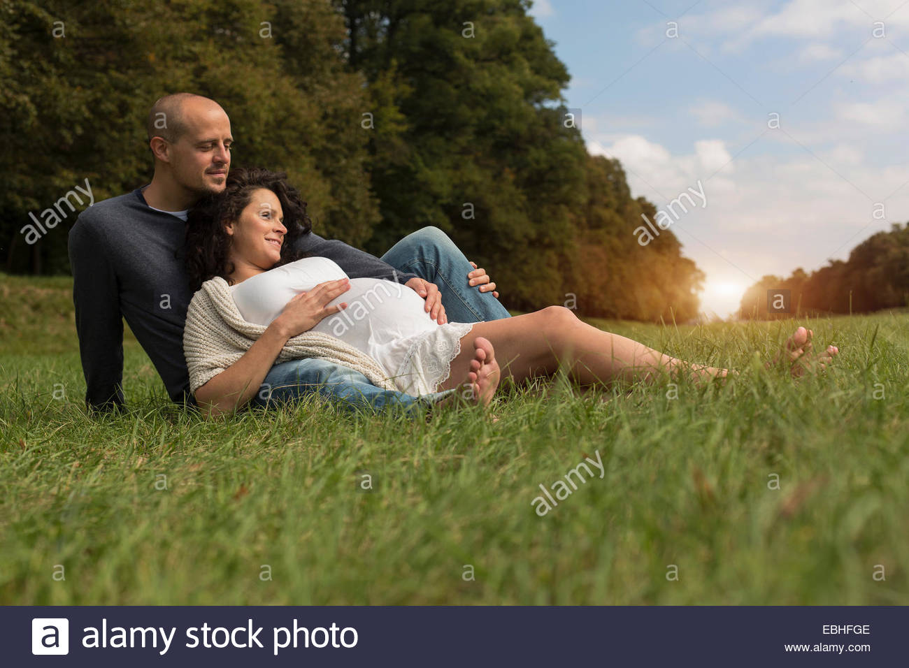 Pregnant couple sitting on grass in park Photo Stock