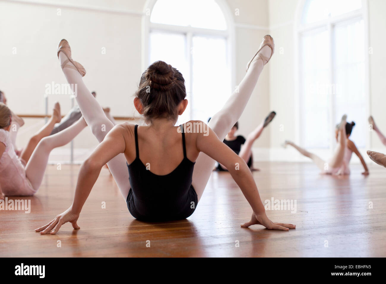Des enfants assis sur le plancher practicing ballet in ballet school Photo Stock