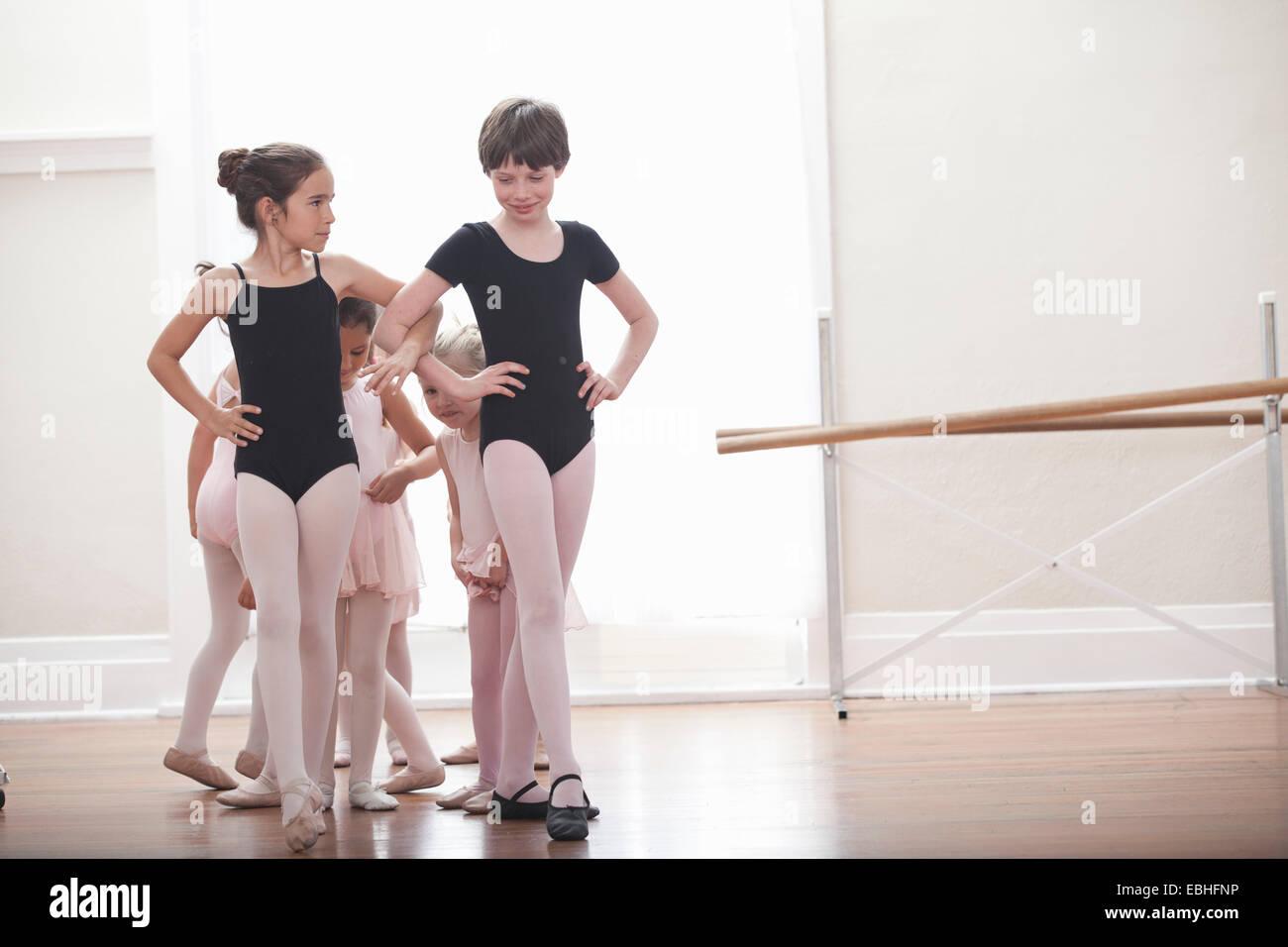 Groupe de filles pratiquant avec les mains sur les hanches en ballet school Photo Stock