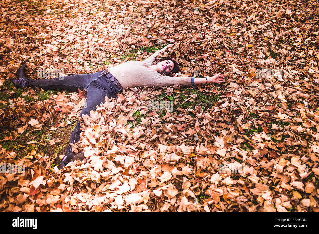 Overhead view of young woman lying on autumn leaves avec bras et jambes tendus Photo Stock