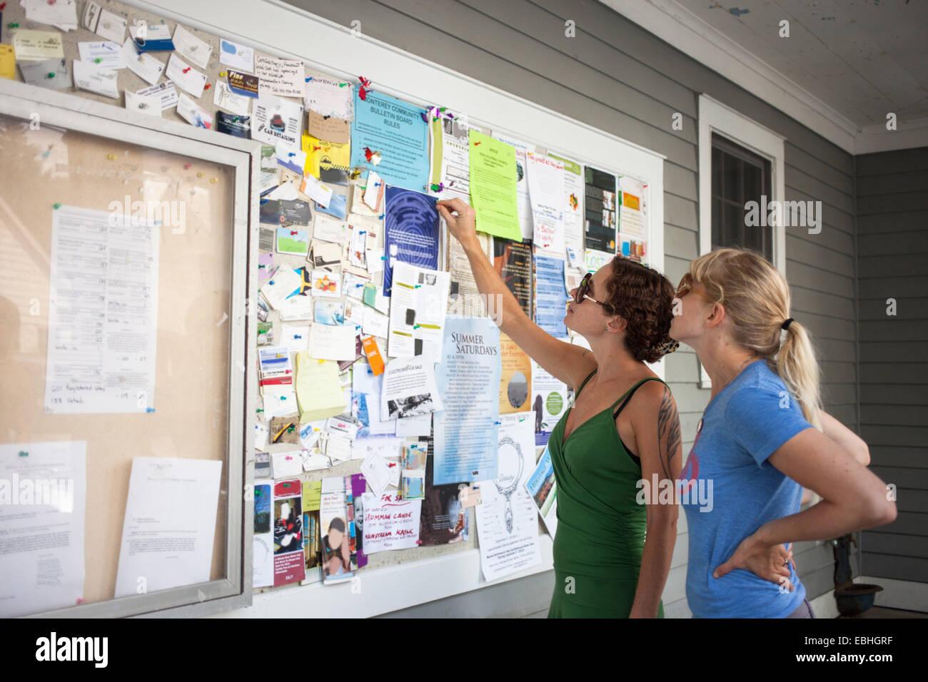 Deux femmes adultes à jusqu'au tableau d'affichage communautaire Photo Stock