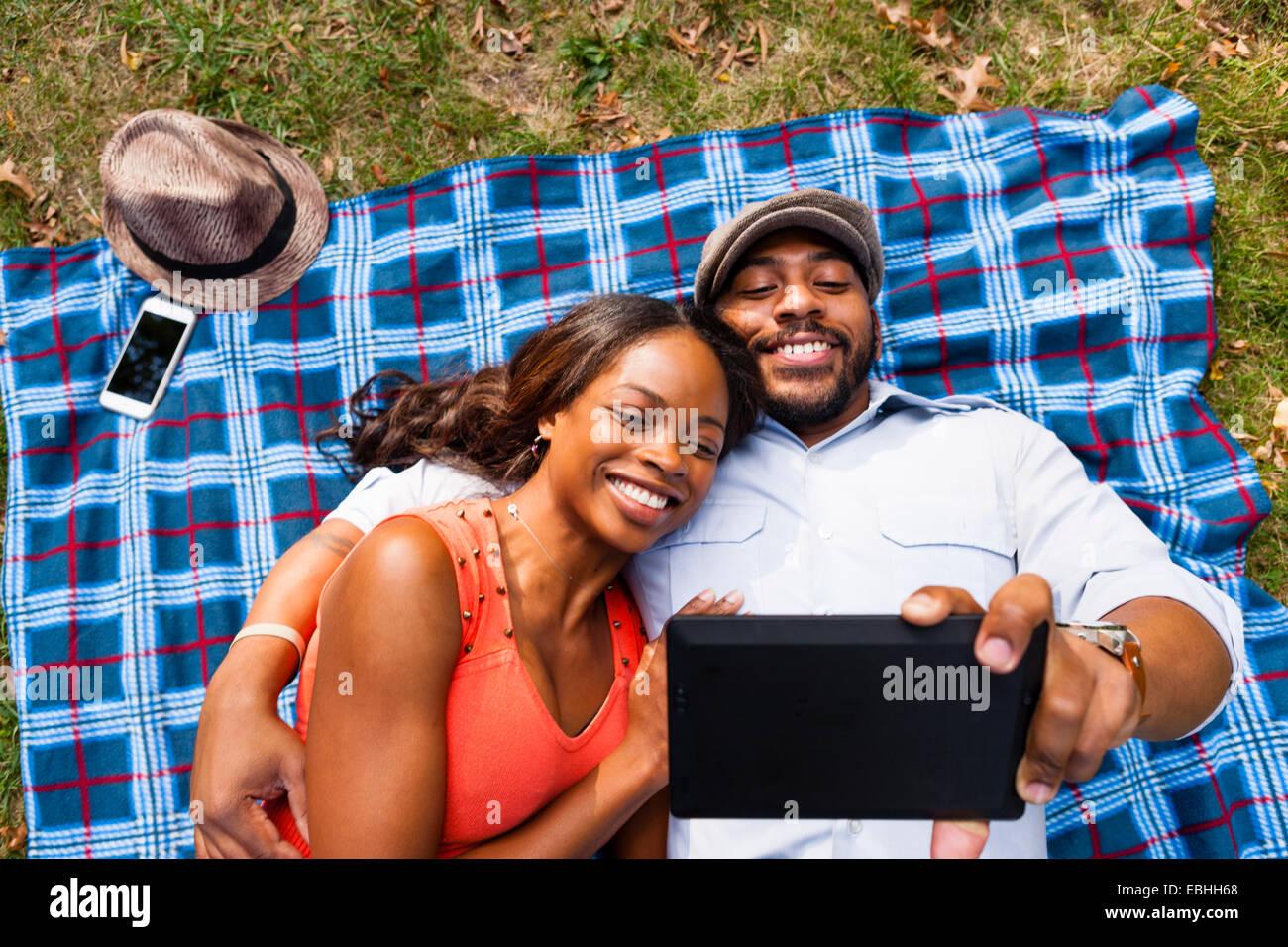 Couple lying on grass regarder la vidéo sur tablette Banque D'Images