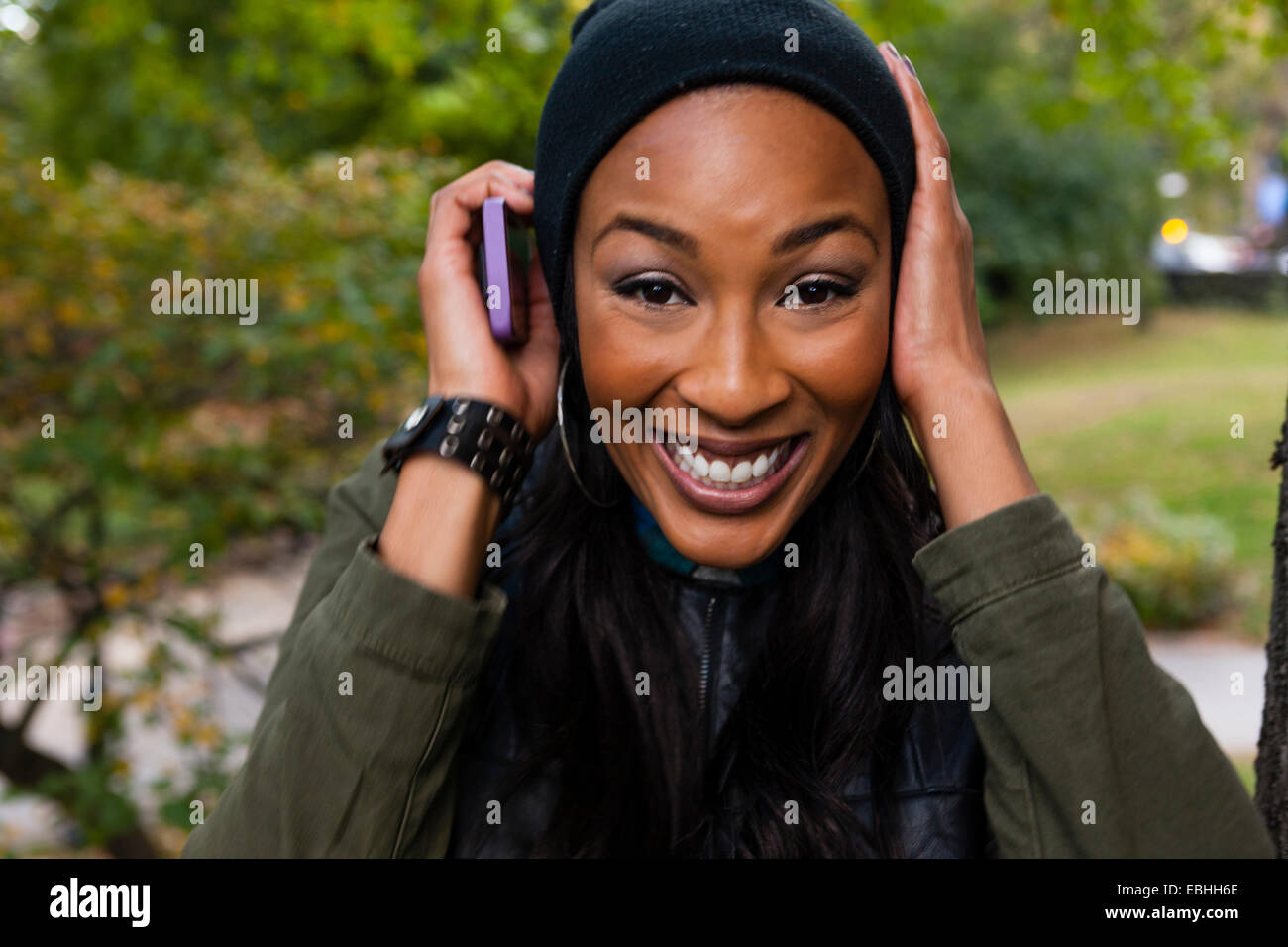 Young woman smiling and holding smartphone à l'oreille Photo Stock