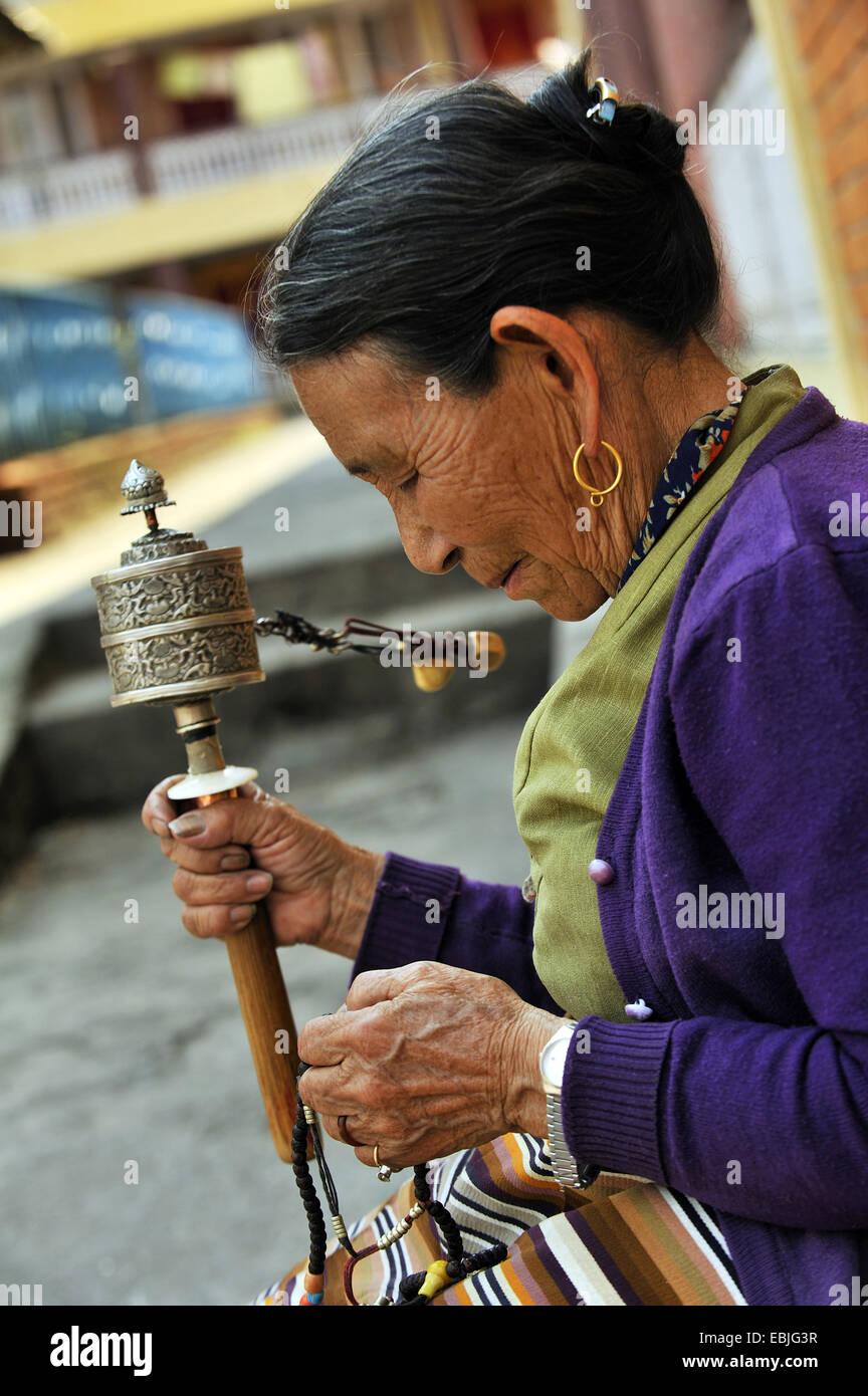 Vieille Femme dans un monastère bouddhiste est coulé dans une prière avec un moulin à prières Photo Stock