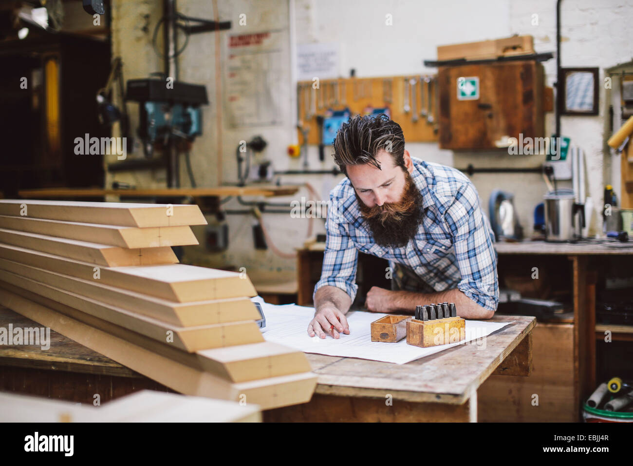Young craftsman regardant le plan directeur dans l'atelier d'organes Photo Stock