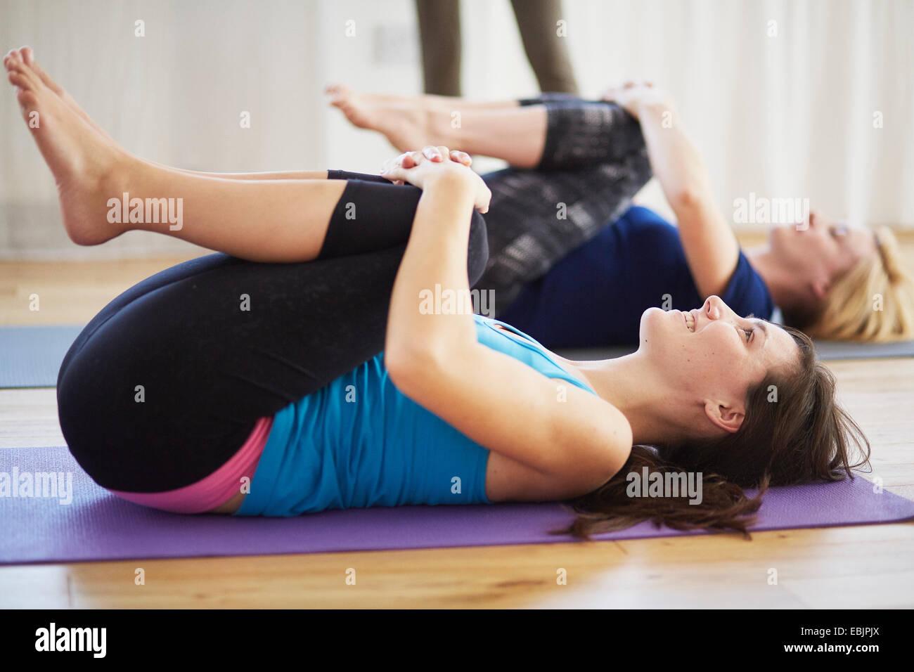 Les élèves de sexe féminin allongé sur le dos en serrant les genoux de pilates Photo Stock