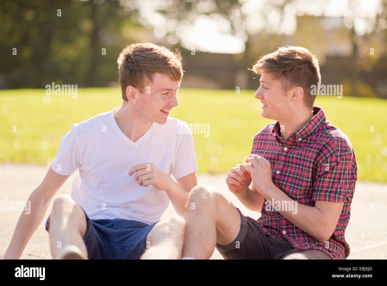Deux jeunes hommes friends chatting in park Photo Stock