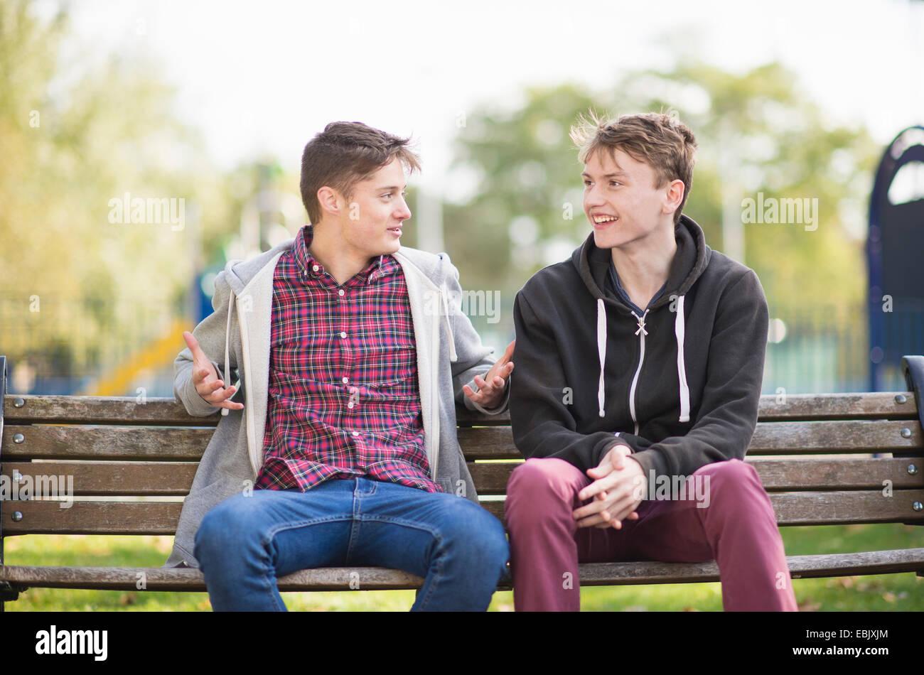 Deux jeunes hommes friends chatting on park bench Photo Stock