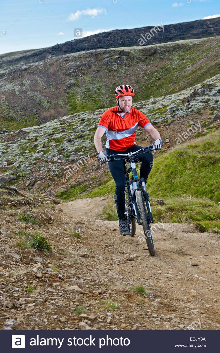 Vélo VTT homme sur un chemin de terre, vallée de Reykjadalur, au sud-ouest de l'Islande Photo Stock