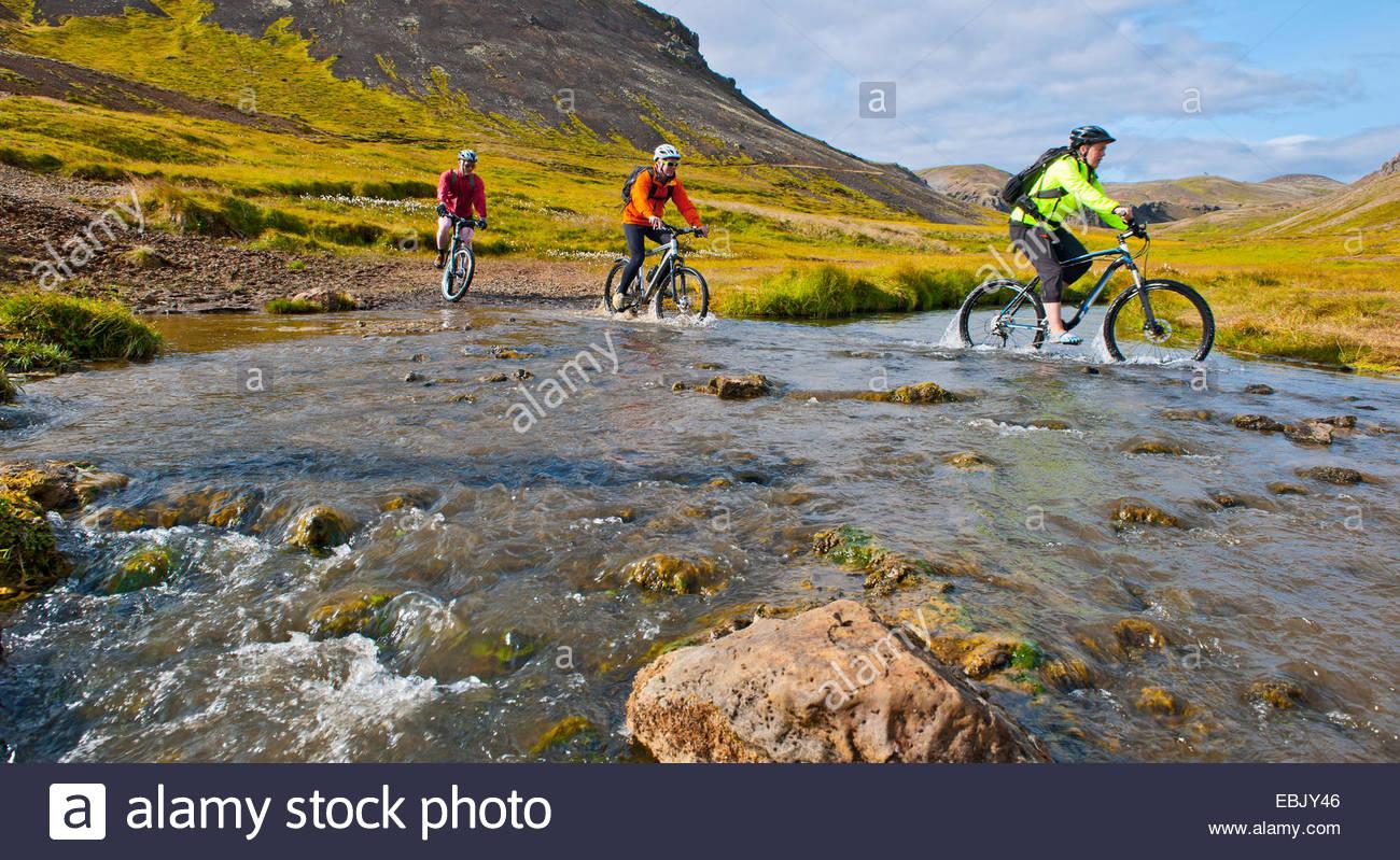 Trois cyclistes de montagne vélo dans la rivière chaude, vallée de Reykjadalur, au sud-ouest de l'Islande Photo Stock