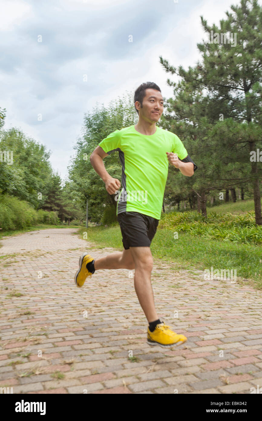 Young male runner running in park Photo Stock