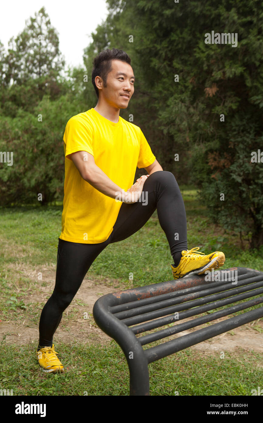 Young male runner stretching leg on park bench in park Photo Stock