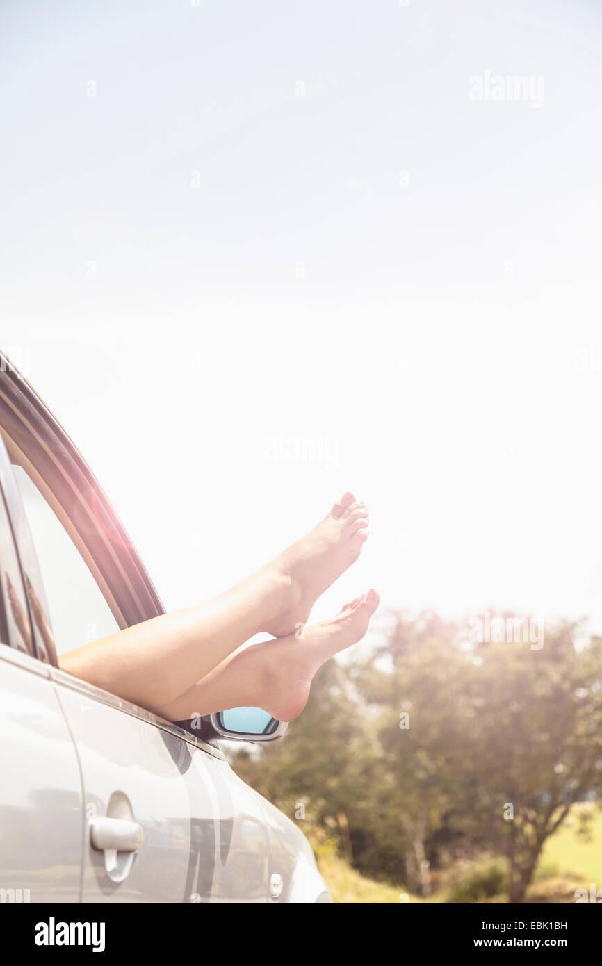 Jeune femme pieds nus reposant sur le pare-brise de voiture Photo Stock
