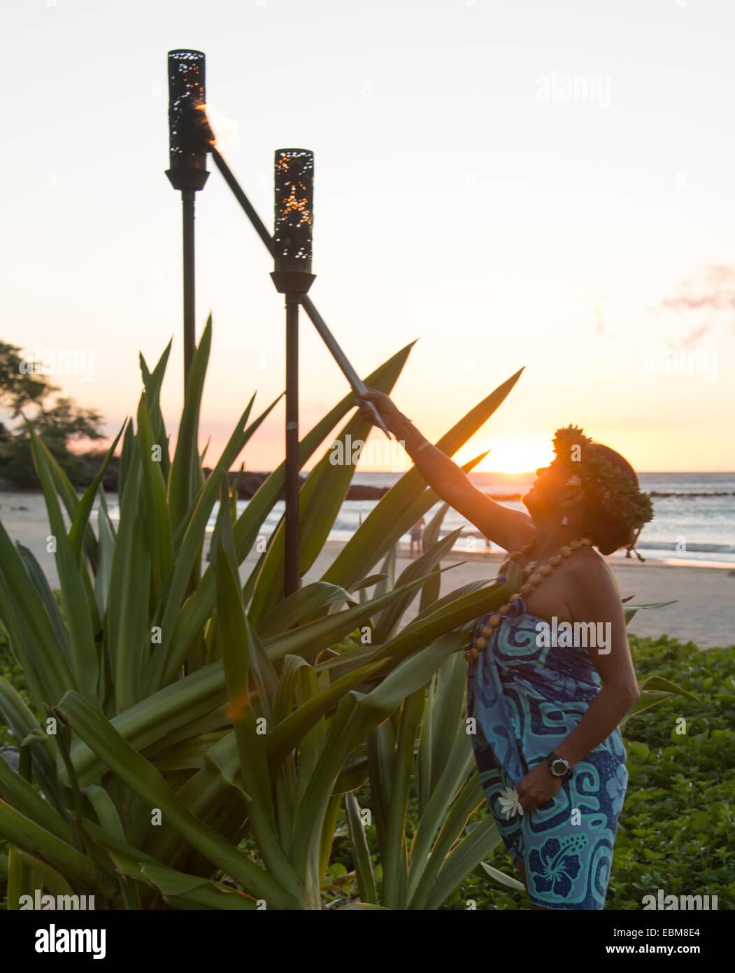 Femme en robe hawaïenne torche tiki des feux sur la plage au coucher du soleil Big Island Hawaii USA Photo Stock