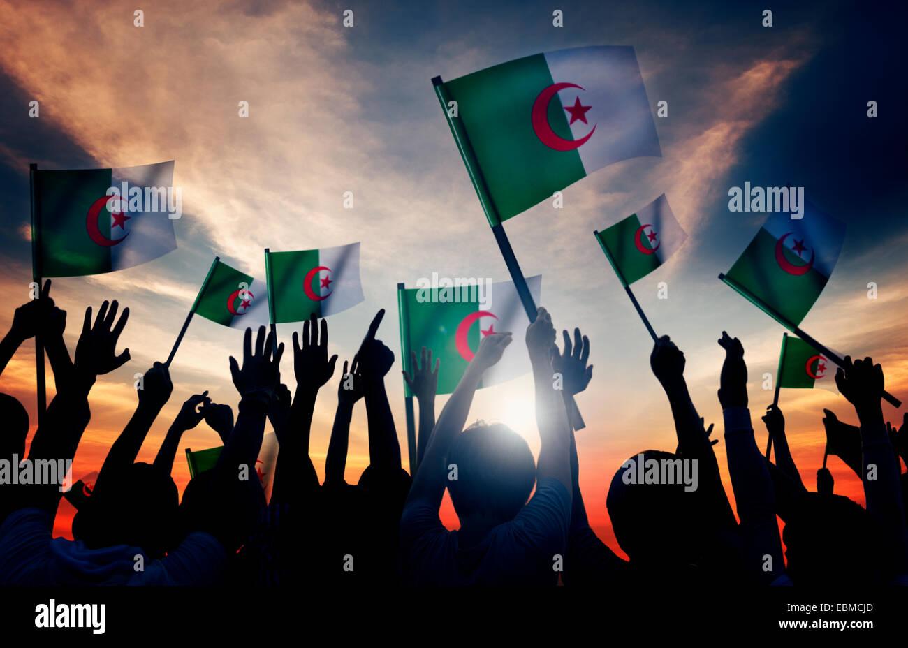 Silhouettes de gens tenant un drapeau de l'Algérie Photo Stock