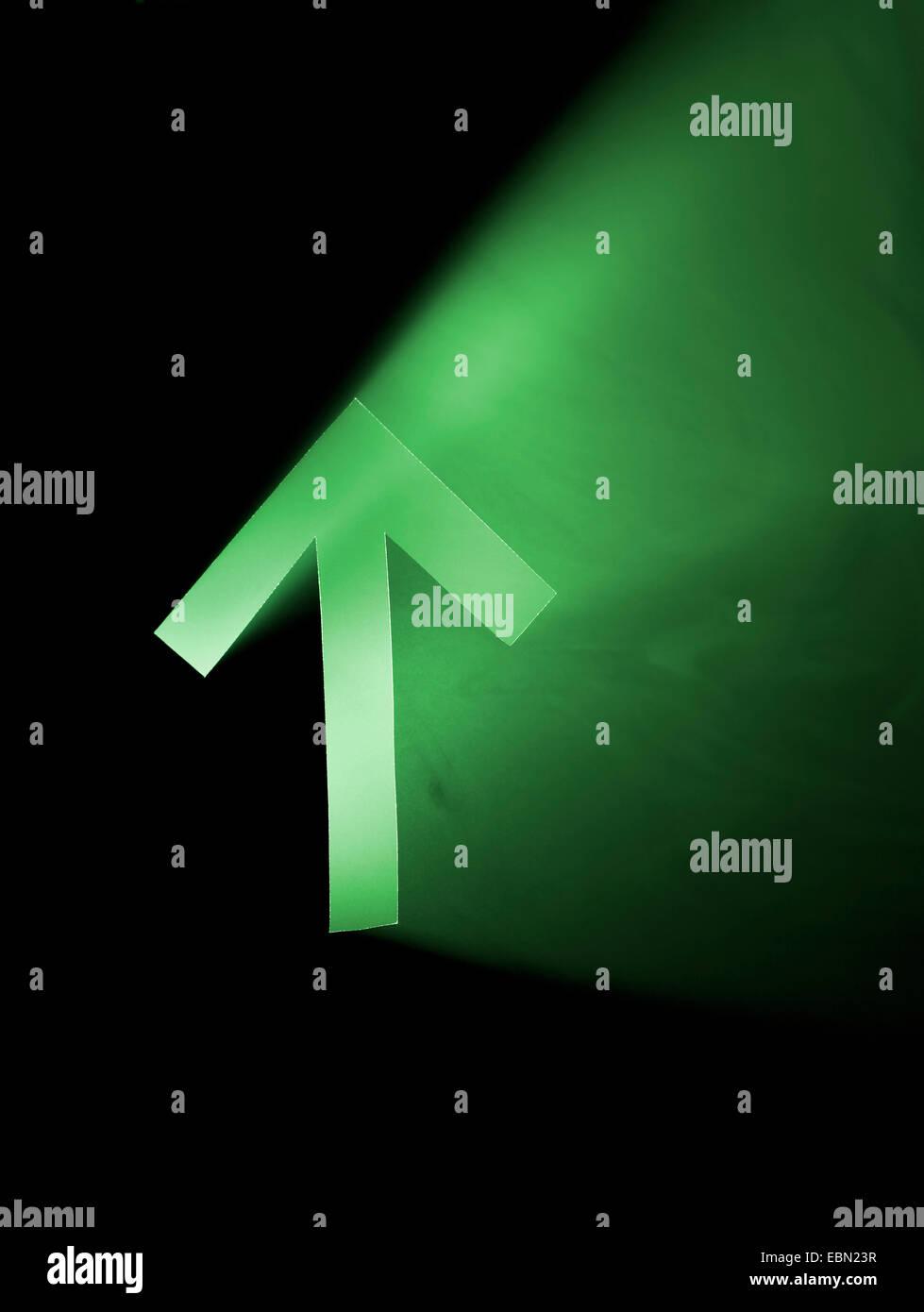 Flèche verte pointe vers le haut. Coupe du trou dans le carton, machine à fumée et des projecteurs. Photo Stock