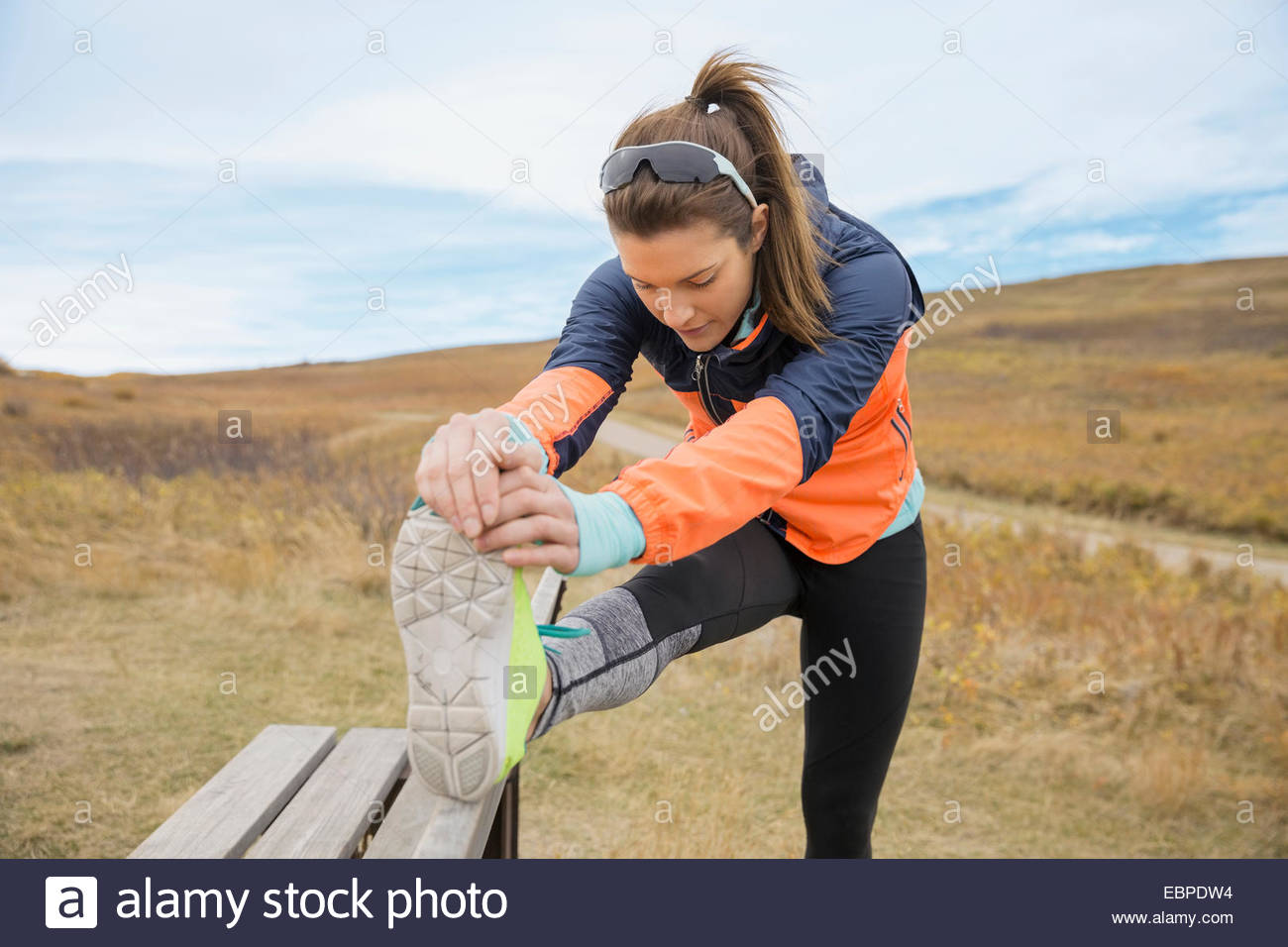 Runner stretching leg sur banc rural Photo Stock