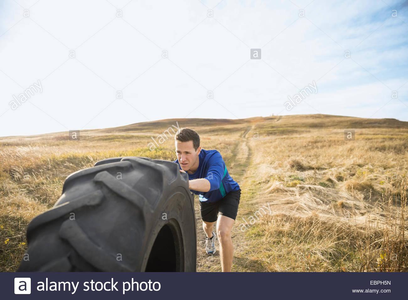 En poussant l'homme dans la ville ensoleillée de pneu crossfit rural field Photo Stock