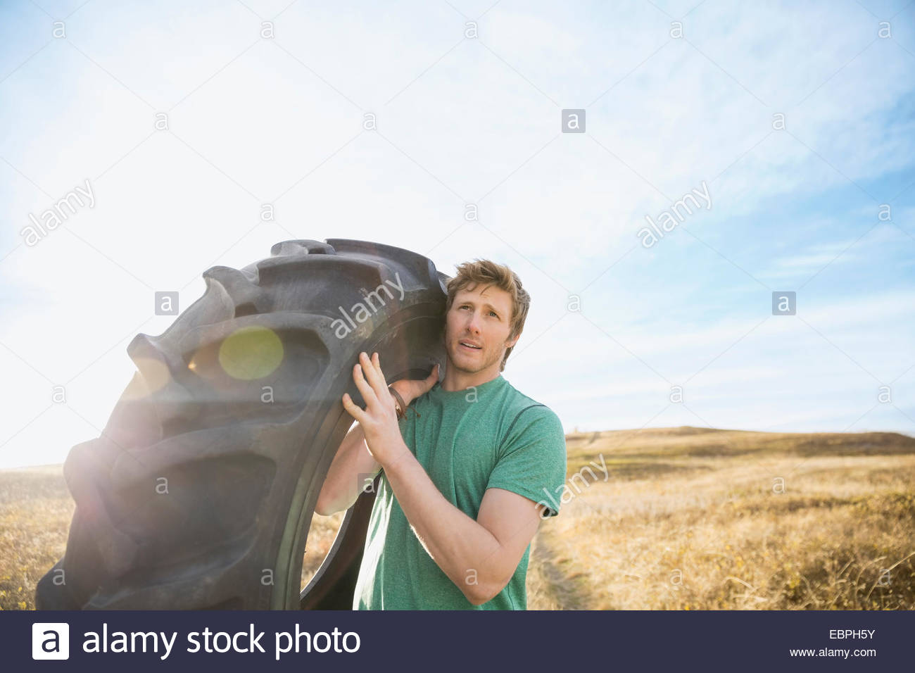 Homme portant des pneus crossfit dans sunny rural field Photo Stock