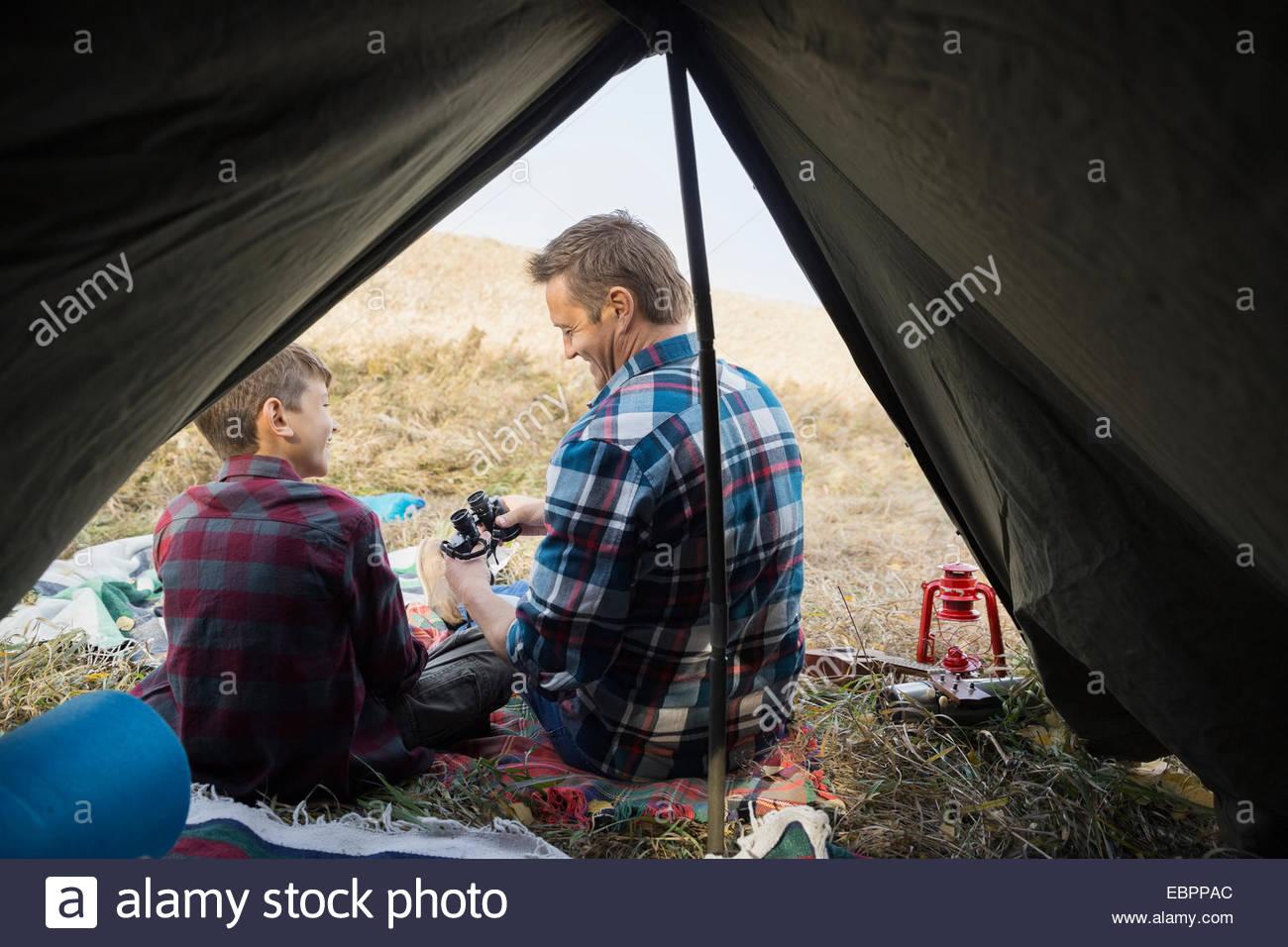 Père et fils avec des jumelles à l'extérieur tente Photo Stock
