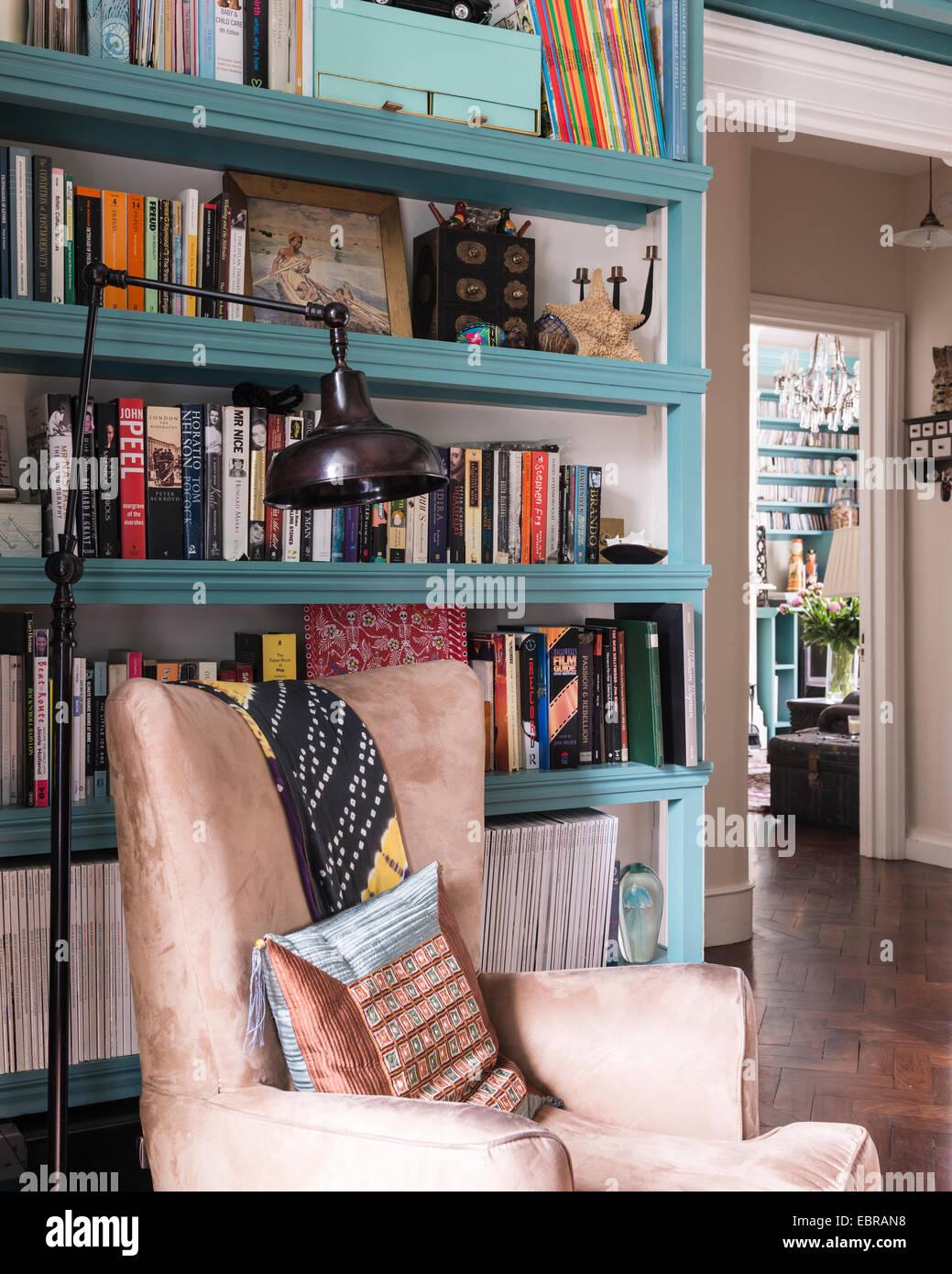 Suede wingback président dans l'étude avec des étagères et de turquoise la mi-siècle Photo Stock