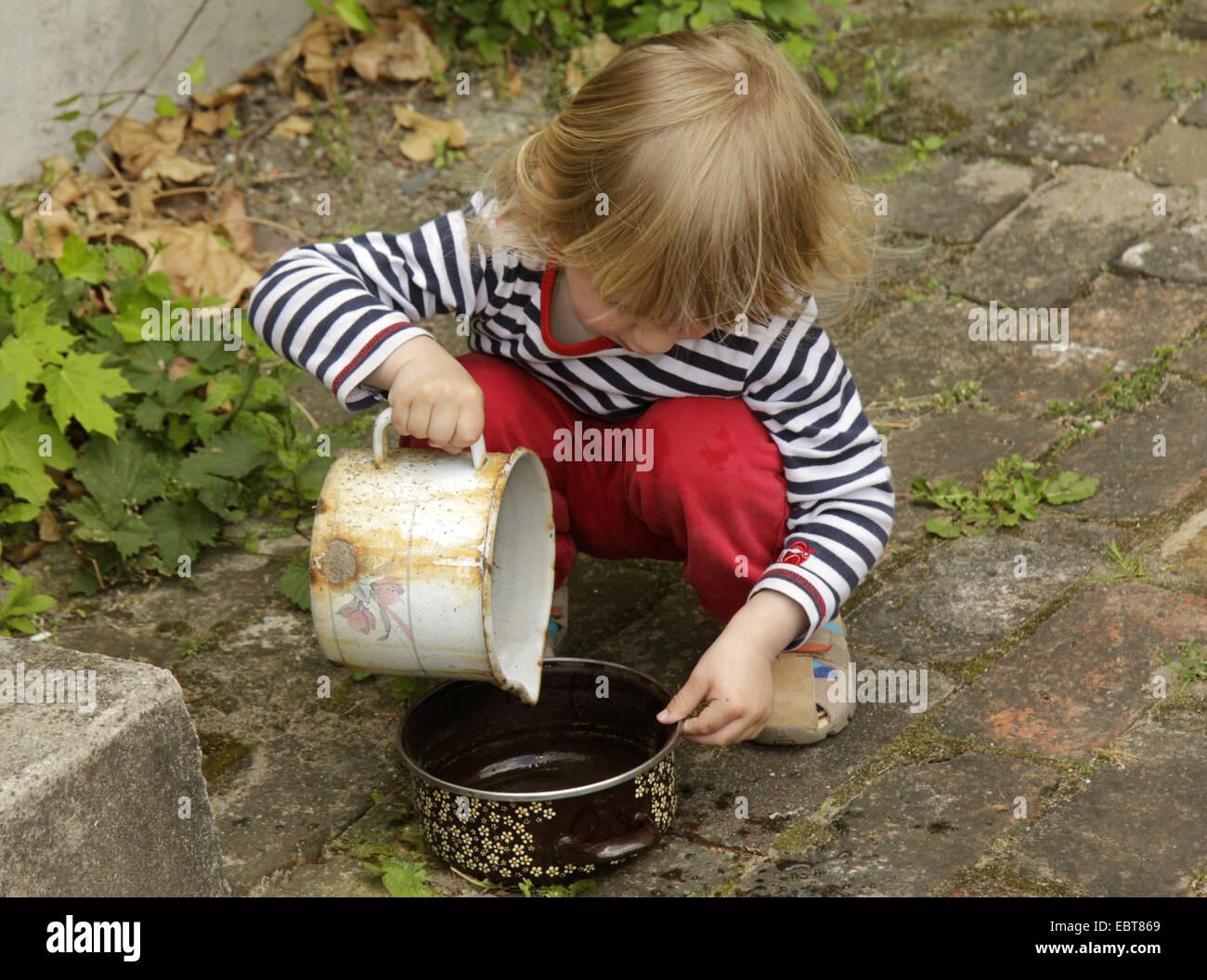 Petit garçon jouer dehors avec l'ancienne batterie de cuisine Photo Stock