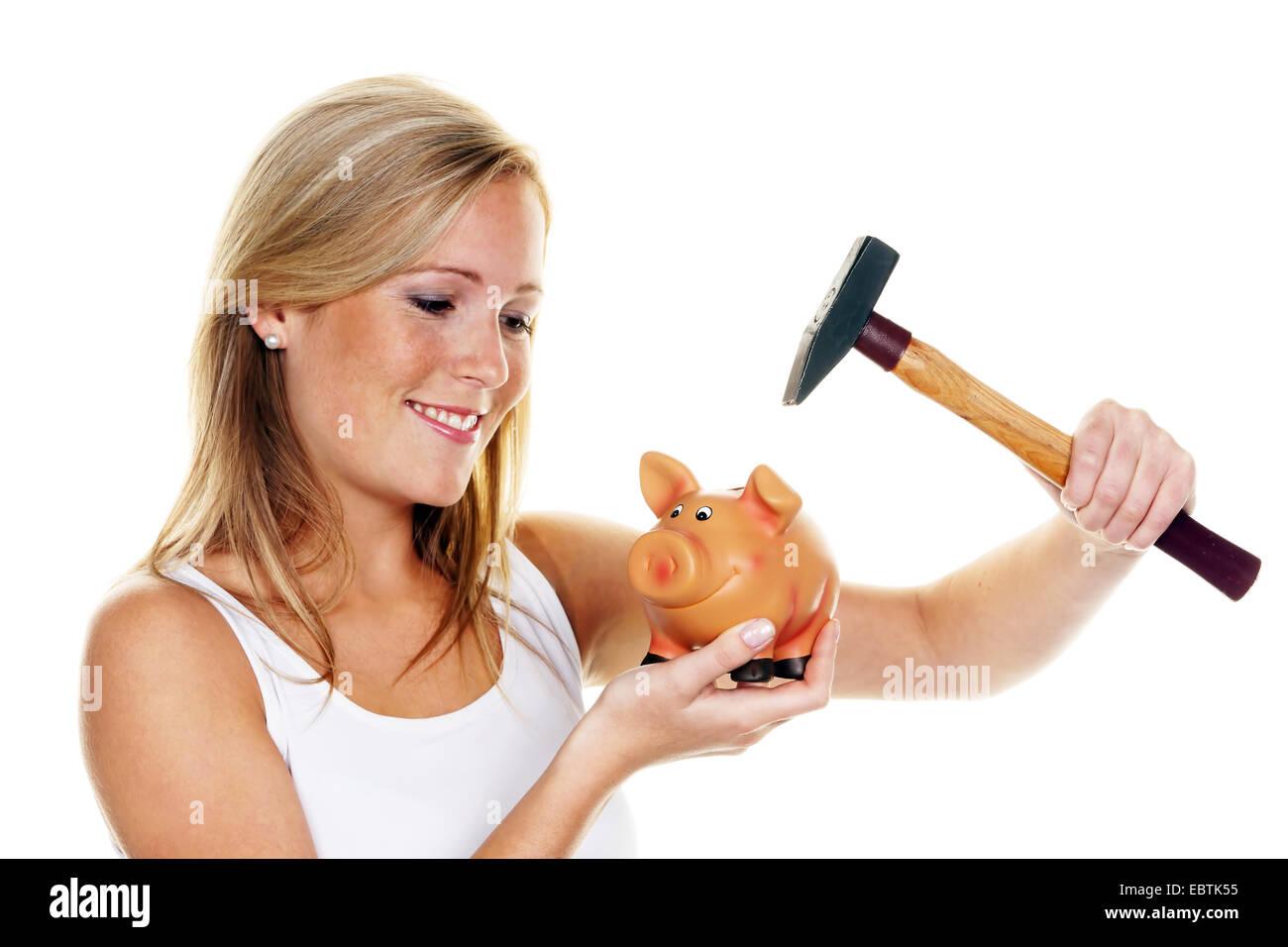 Jeune femme avec un marteau tuant sa tirelire Banque D'Images