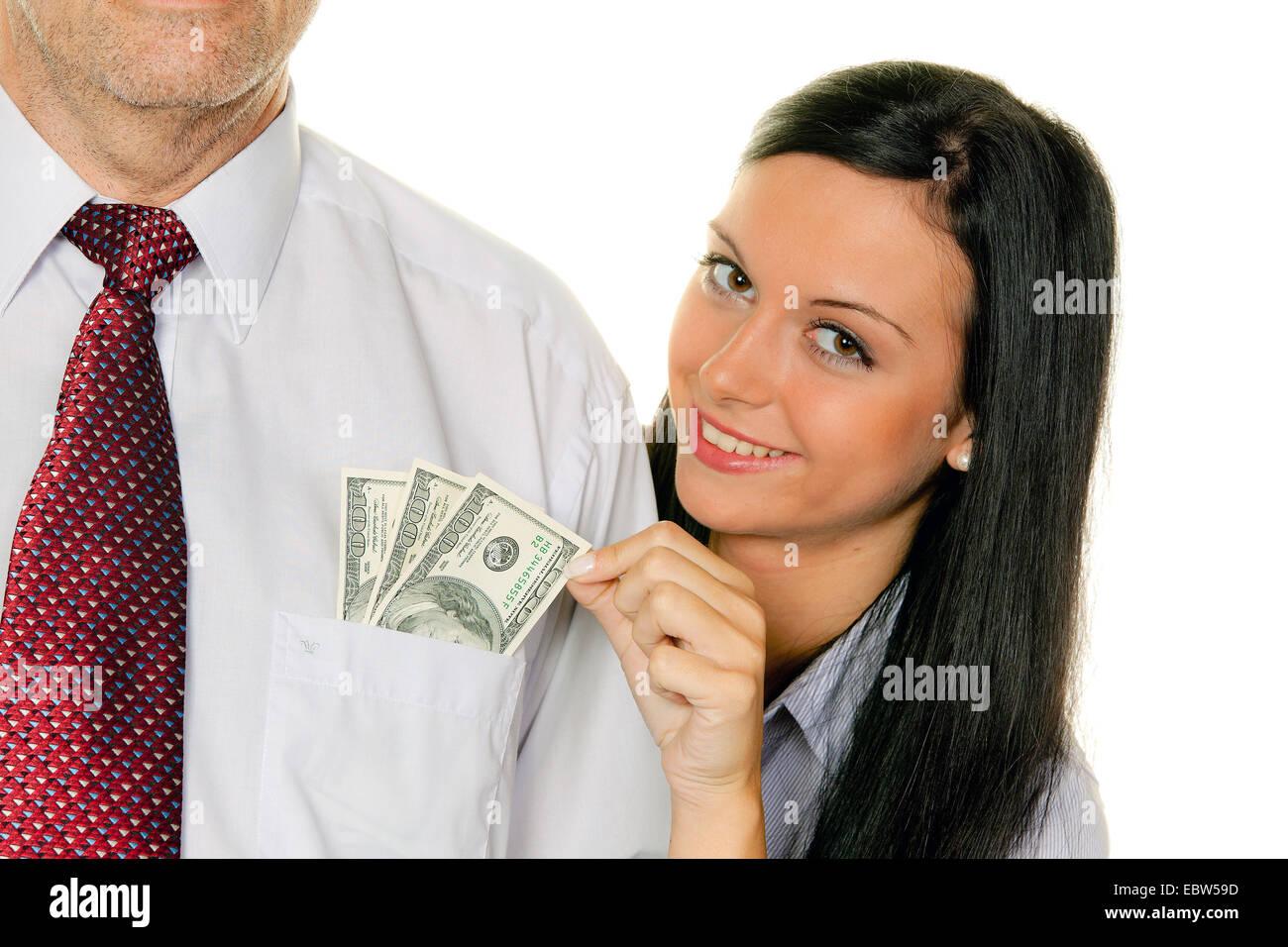 Jeune femme squeeze de l'argent d'un homme Photo Stock