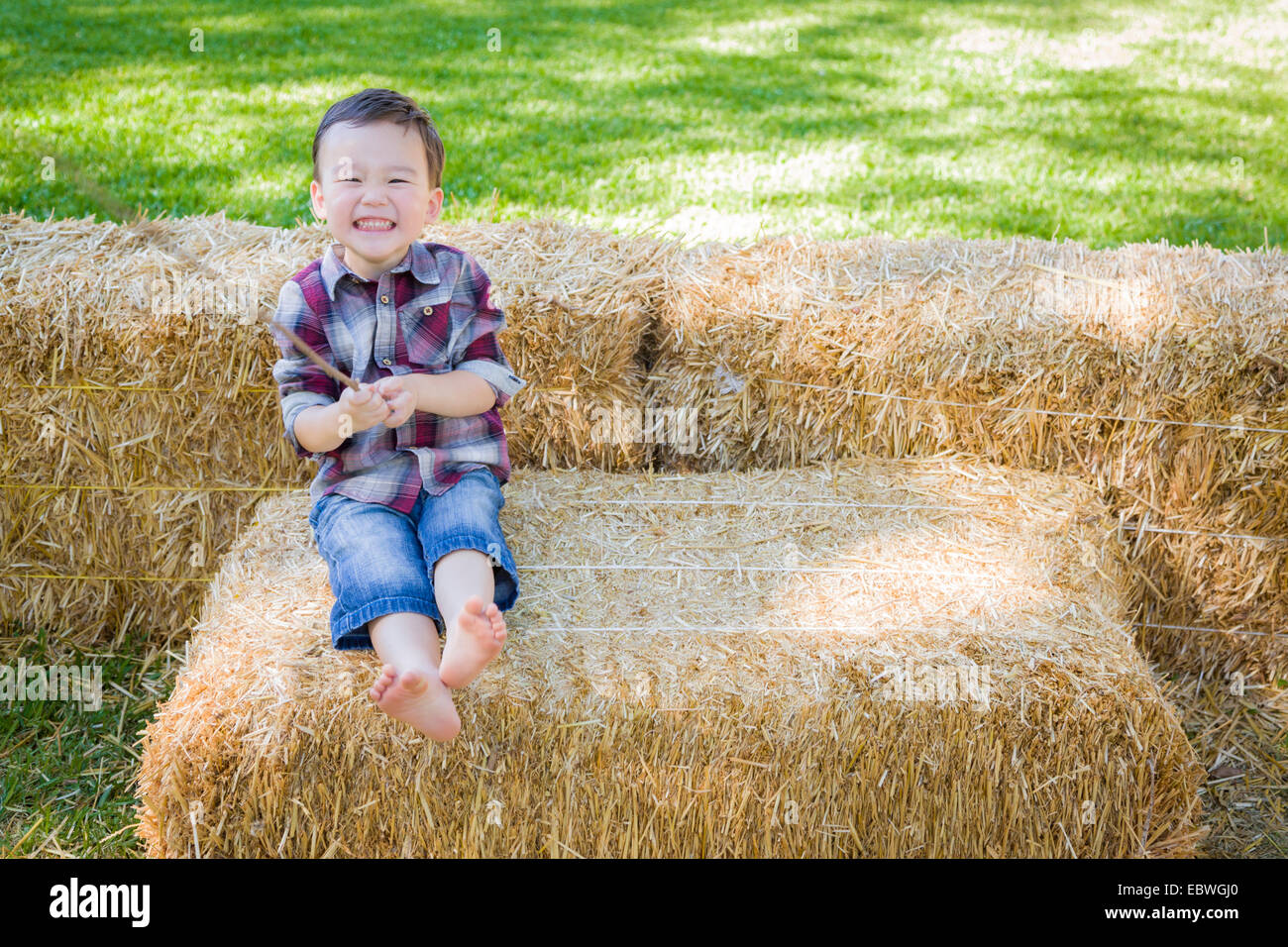 Cute Young Mixed Race Boy having fun on Hay Bale à l'extérieur. Photo Stock