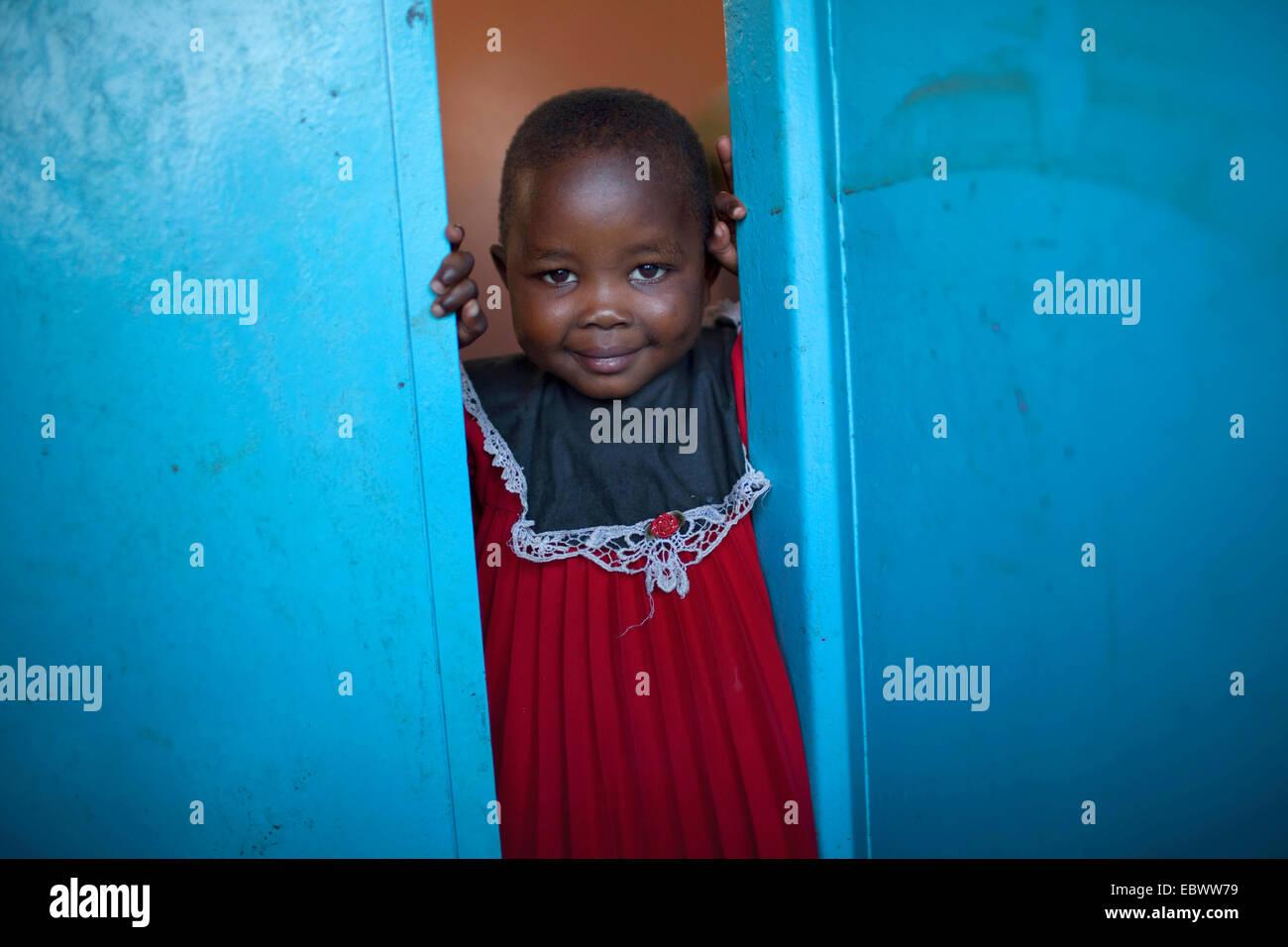 Petite fille dans un tissu rouge à la recherche d'une porte bleue, BURUNDI, Bujumbura Mairie, Bujumbura Banque D'Images