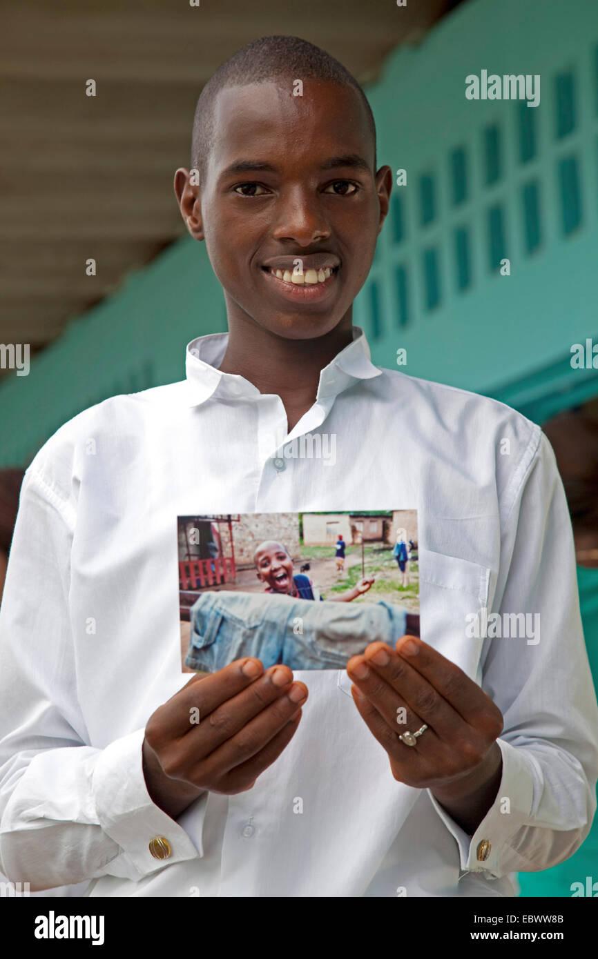 Garçon sourit tout en maintenant une photographie de pair avec lui-même sur elle, BURUNDI, Bujumbura Mairie, Photo Stock
