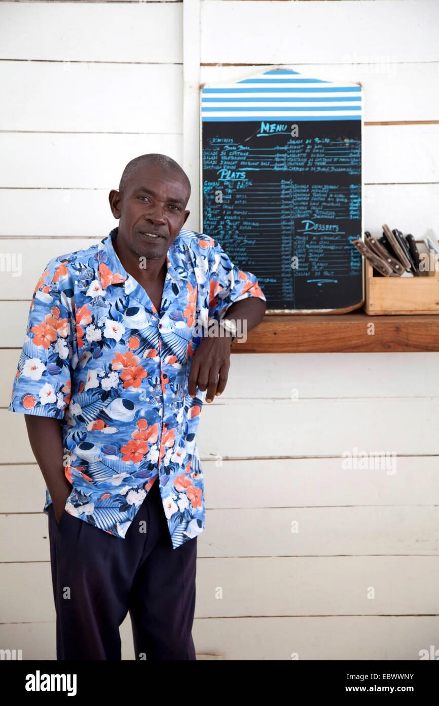 Homme debout à un comptoir avec des couverts et menu, BURUNDI, Bujumbura Mairie, Bujumbura Photo Stock