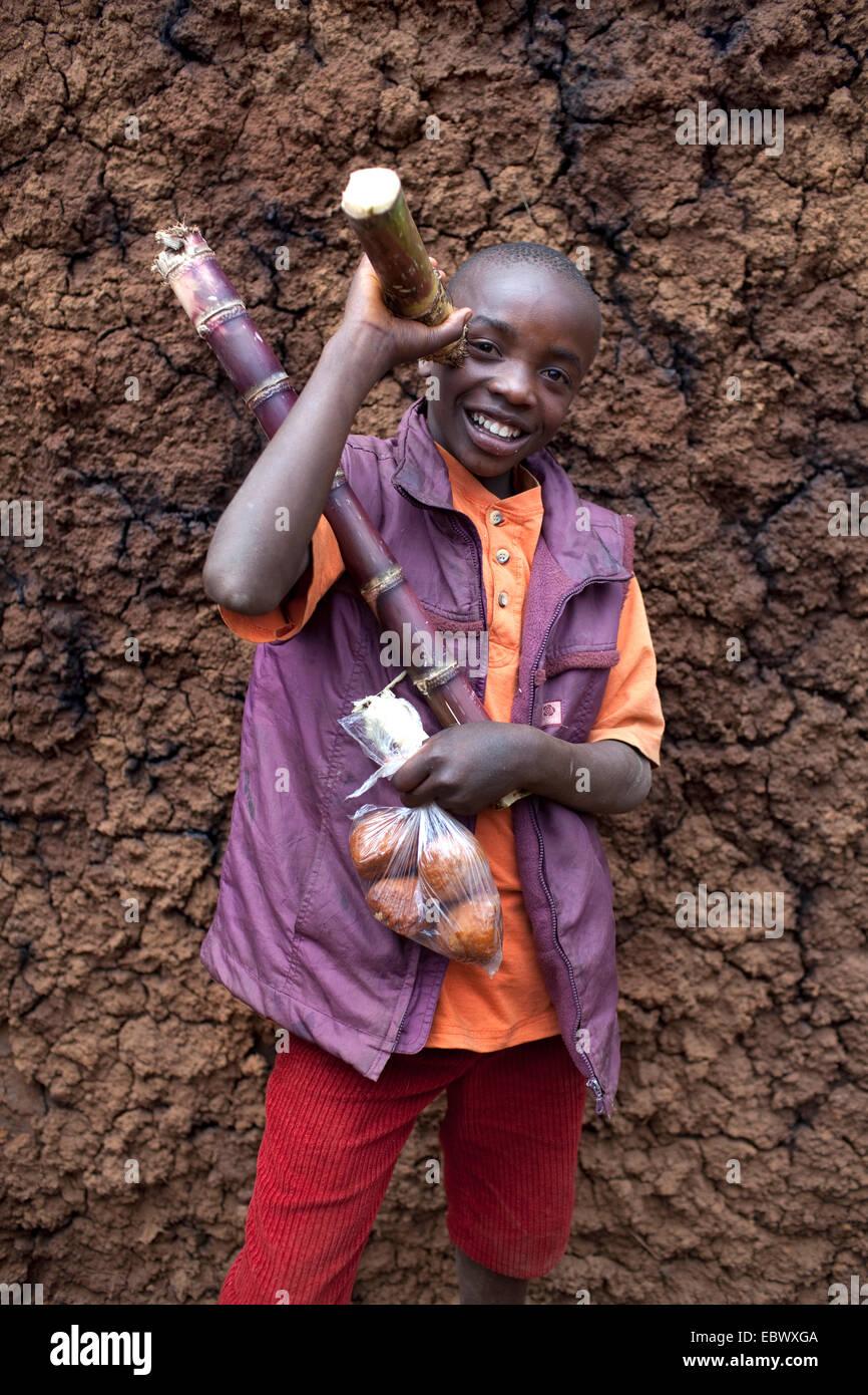 Portrait d'un garçon avec de la canne à sucre et un sac avec des produits de boulangerie, Burundi, Photo Stock