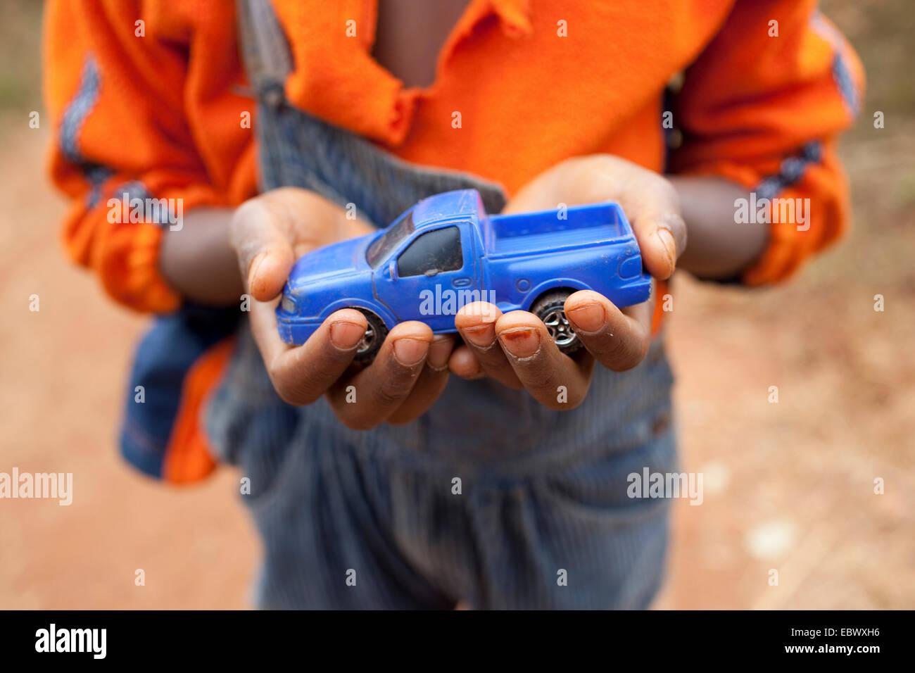 Garçon tenant une petite voiture bleue dans ses mains, le Burundi, Karuzi, Buhiga Photo Stock