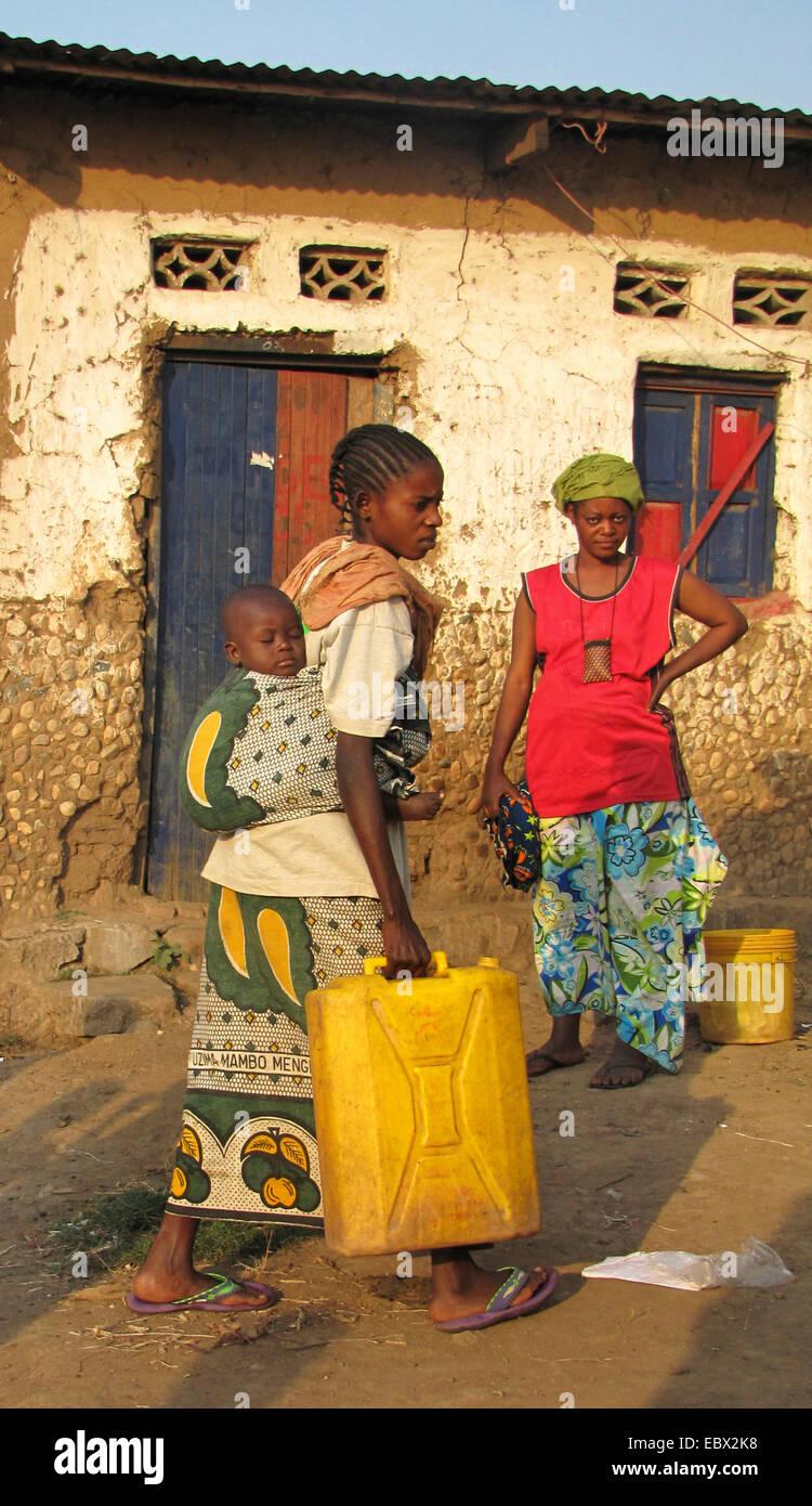 Les femmes à la zone pauvre de la capitale, prenant l'eau dans leurs foyers en boîtes, bébé Photo Stock