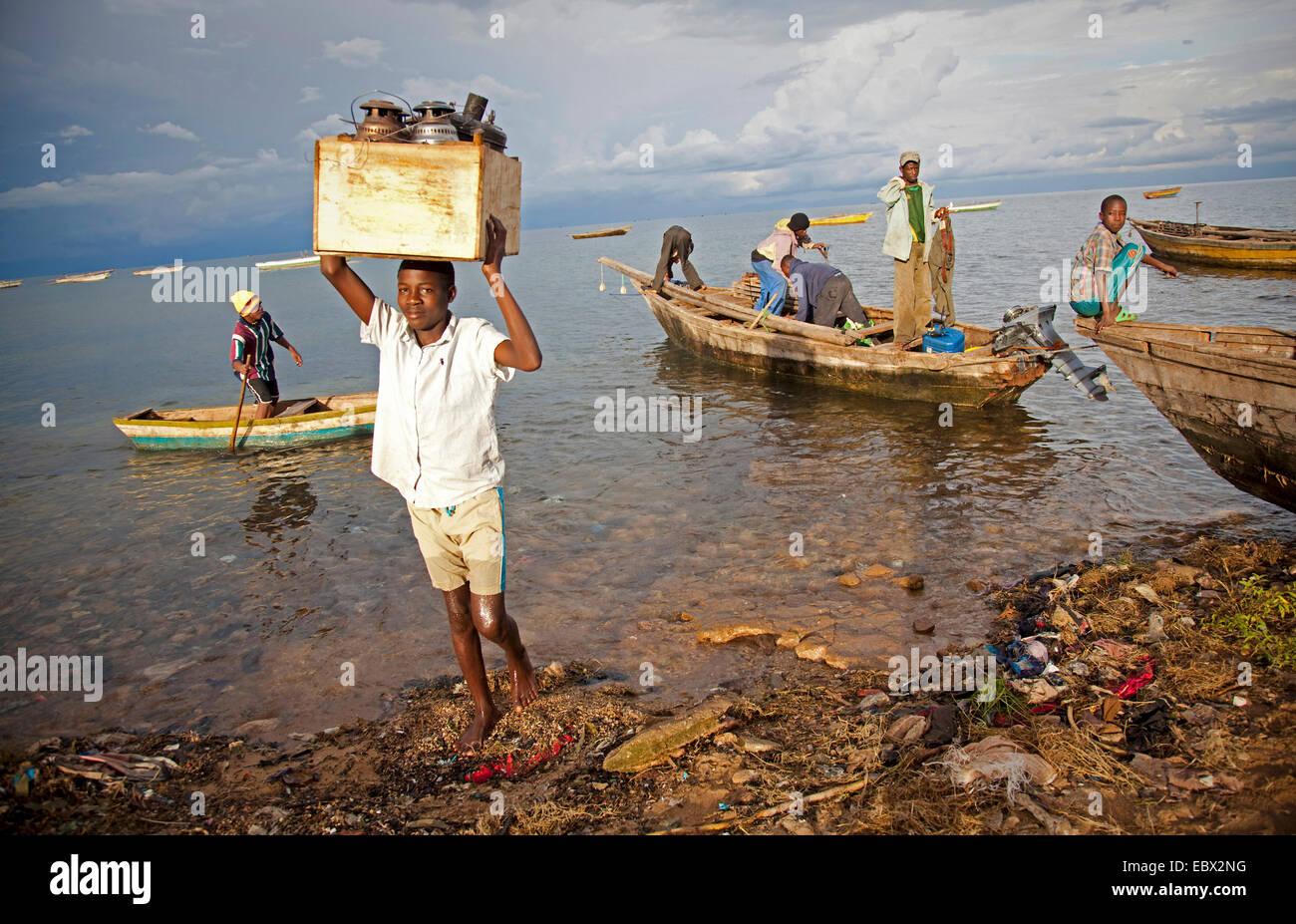 Un garçon portant un fort avec des lampes à l'huile de bateau de pêche, le lac Tanganyika, le Burundi, Makamba, Banque D'Images