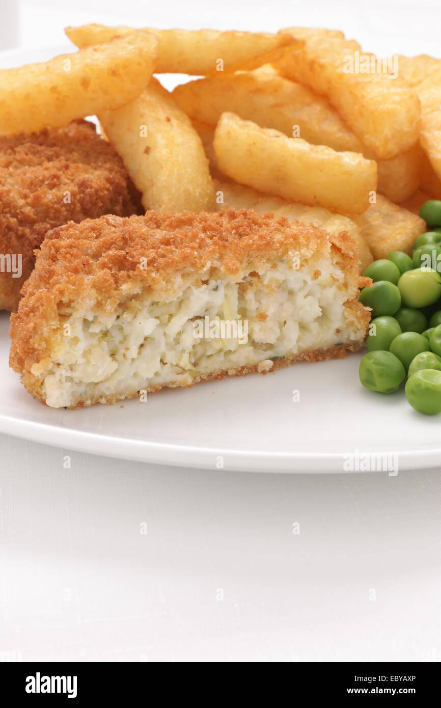Fait crumbed Fishcake avec poisson et pommes de terre servis avec frites et petits pois Photo Stock