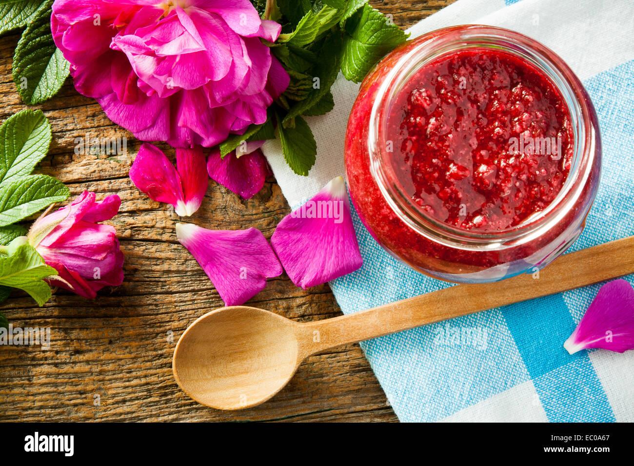 Des confitures faites à partir de damas rose pétale sur table en bois. Selective focus Photo Stock