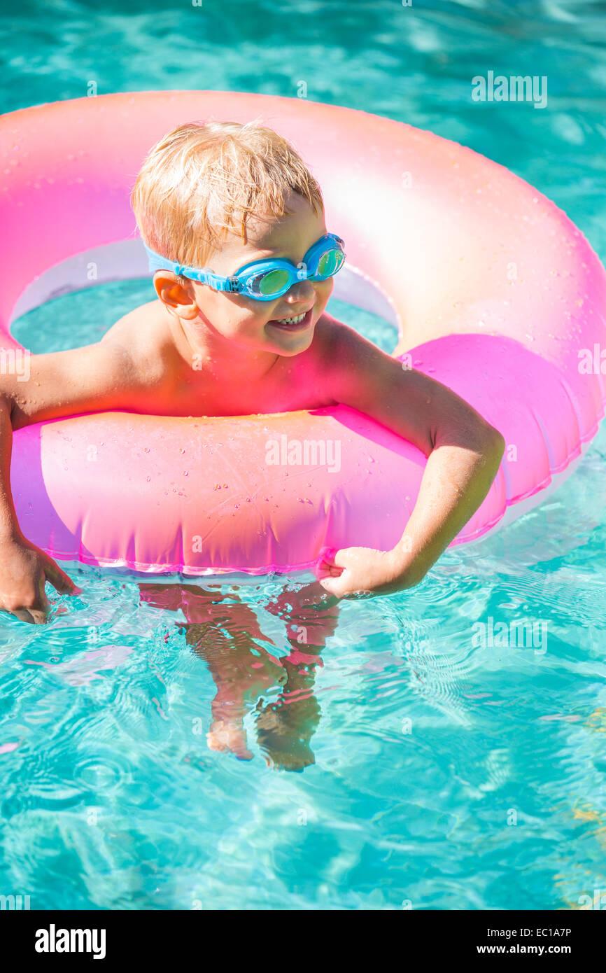 Petit Enfant s'amusant dans la piscine, avec lunettes et radeau. Plaisir de vacances d'été. Photo Stock