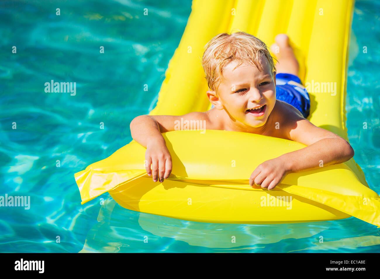 Jeune garçon se détendre et s'amuser dans la piscine sur radeau jaune. Plaisir de vacances d'été. Photo Stock
