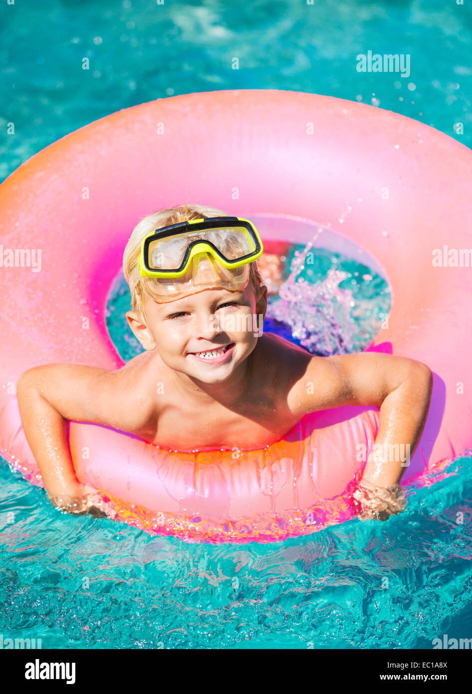 Jeune garçon s'amusant dans la piscine sur le tube intérieur radeau. Plaisir de vacances d'été. Photo Stock