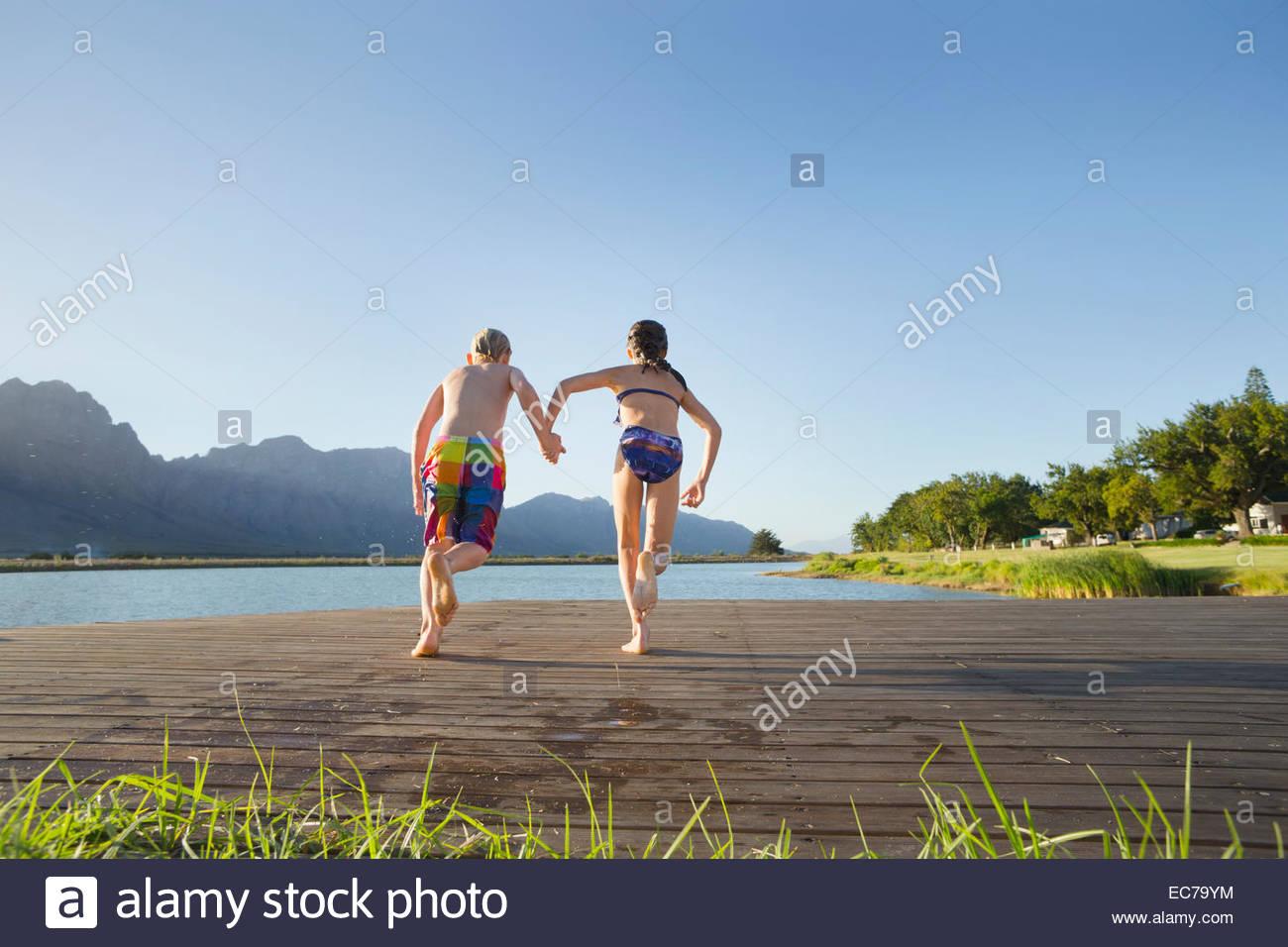 Les enfants dans le bain, la course de sauter dans un lac d'une jetée Photo Stock