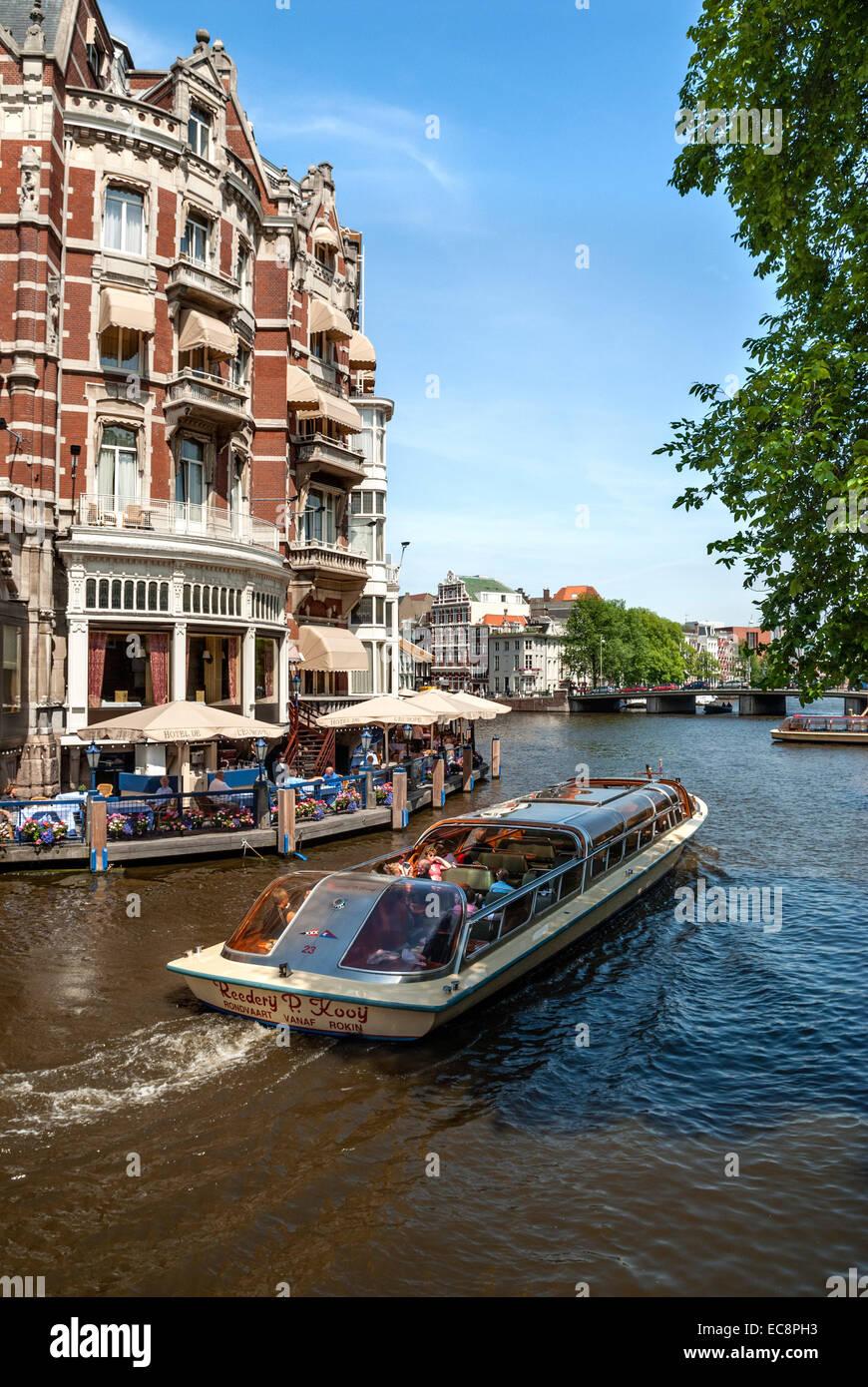 Bateaux de la conduite dans un canal d'eau dans le centre-ville d'Amsterdam, Hollande. Banque D'Images