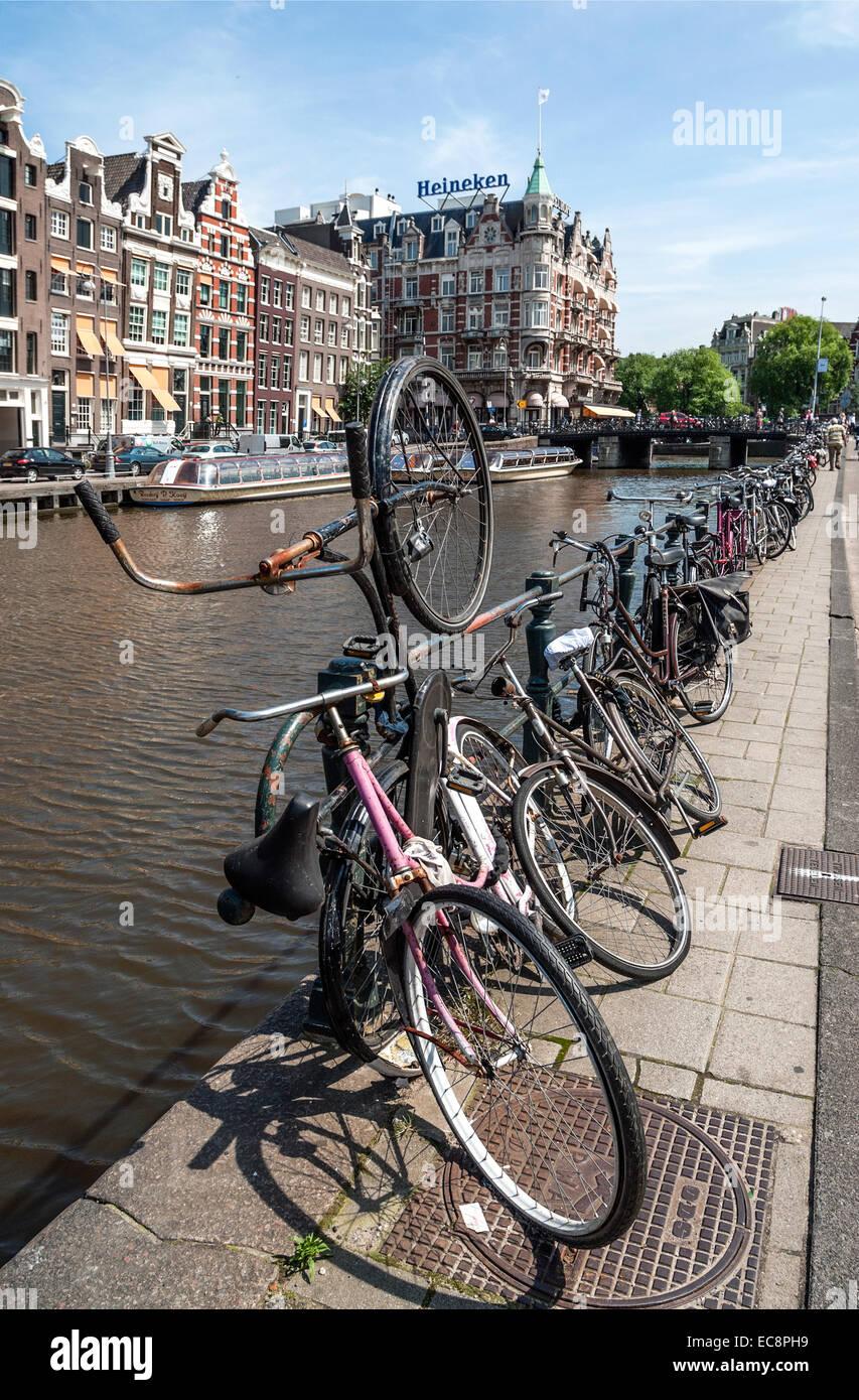 Vieux vélos garés sur une gracht dans le centre-ville d'Amsterdam, Pays-Bas. Banque D'Images