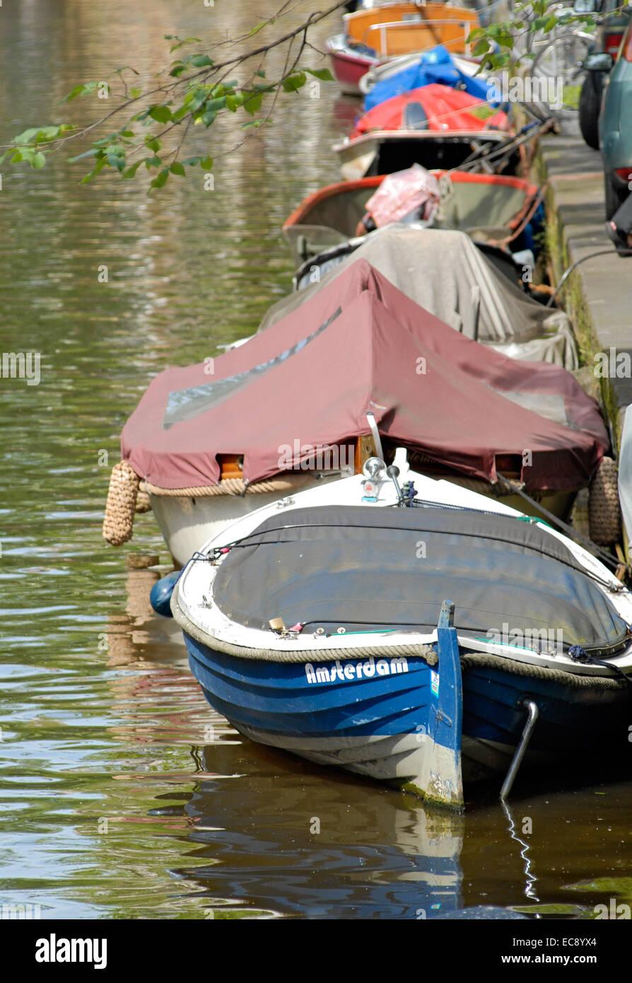 Les petits bateaux dans un canal d'eau dans le centre-ville d'Amsterdam, Pays-Bas. Banque D'Images