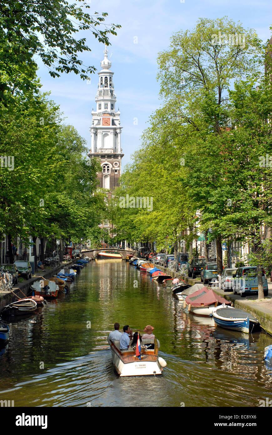 Petite embarcation à moteur au volant dans un canal d'eau dans le centre-ville d'Amsterdam, Pays-Bas avec l'Oude Kerk en arrière-plan. Banque D'Images