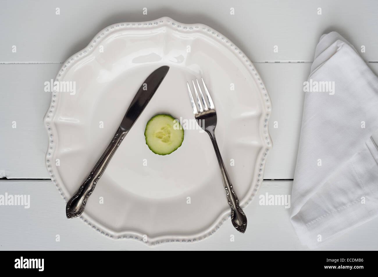 Perte de poids - le concept de l'an seule tranche de concombre sur une plaque Photo Stock